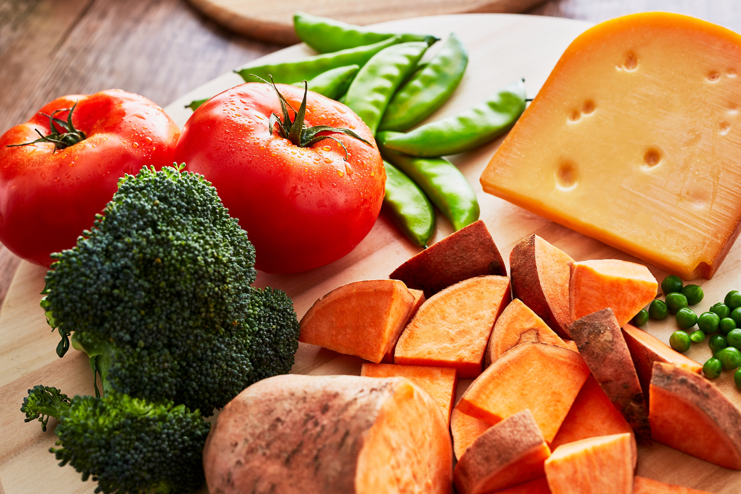 A commercial, lifestyle, fashion, advertising image of fresh ingredients, like tomato, broccoli, sweet potatoe and peas - taken by Javier Edwards of El Roi Photo, in Miami, Florida