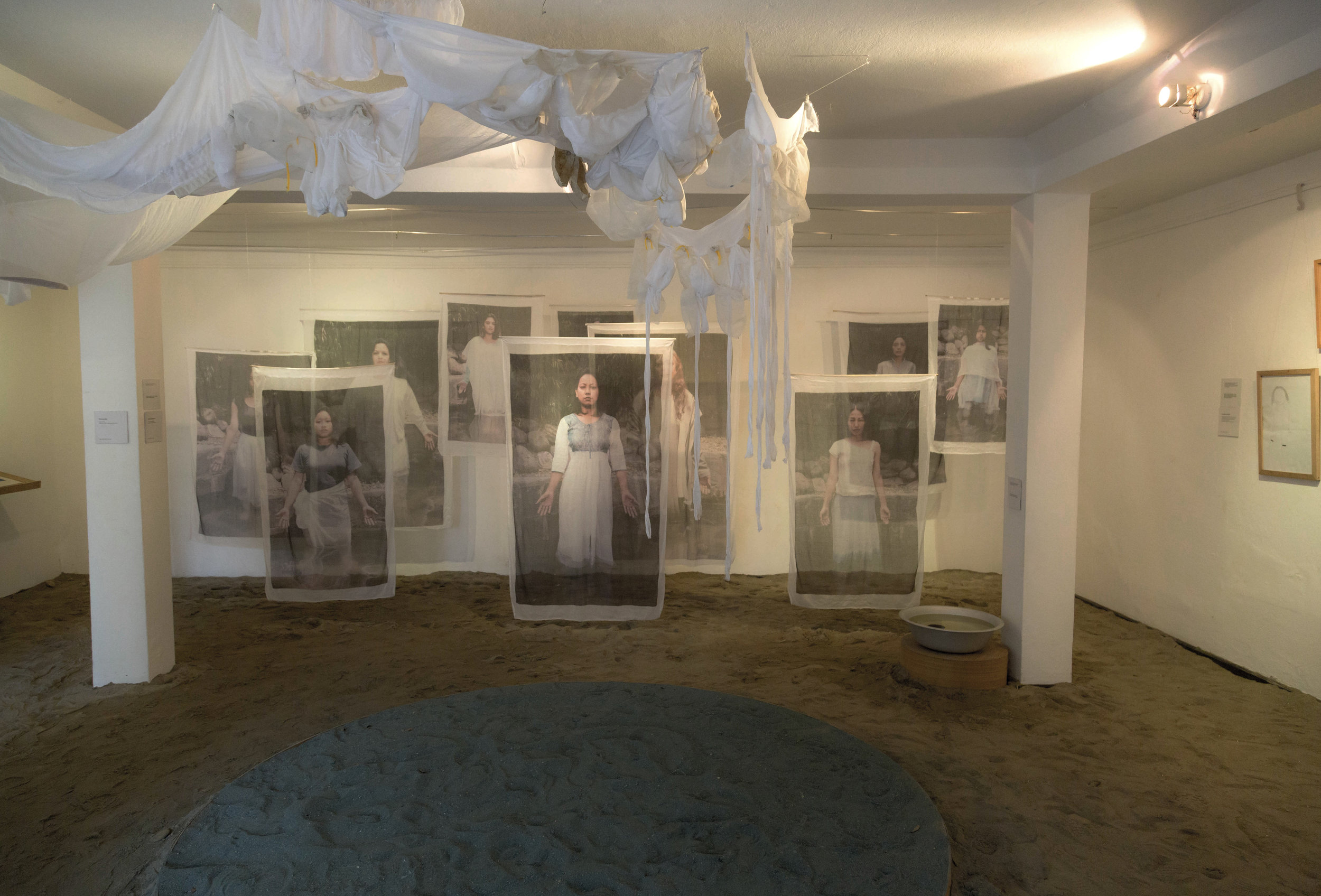 Ground floor of the exhibition, featuring sand installation and raised platform for performances.