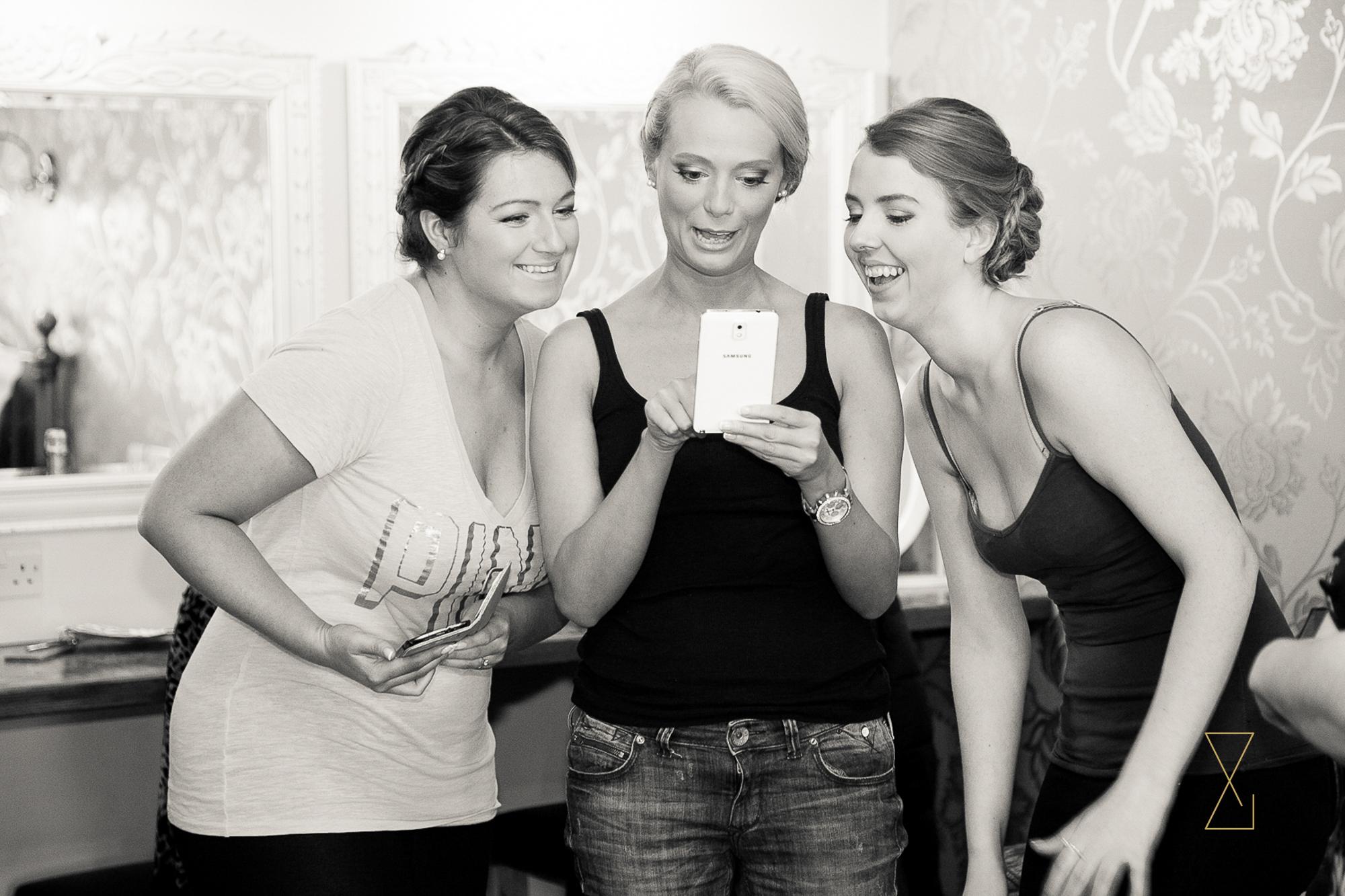 Bridesmaid reviewing a selfie at Heaton House Farm, Evans & Evans wedding photography