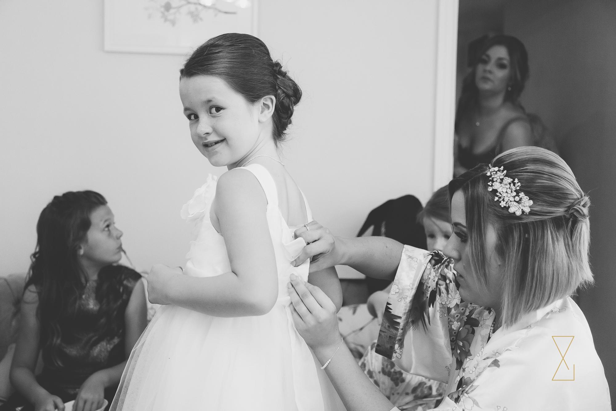 A little flower girl in her dress at Sandhole Oak Barn, Evans & Evans wedding photography