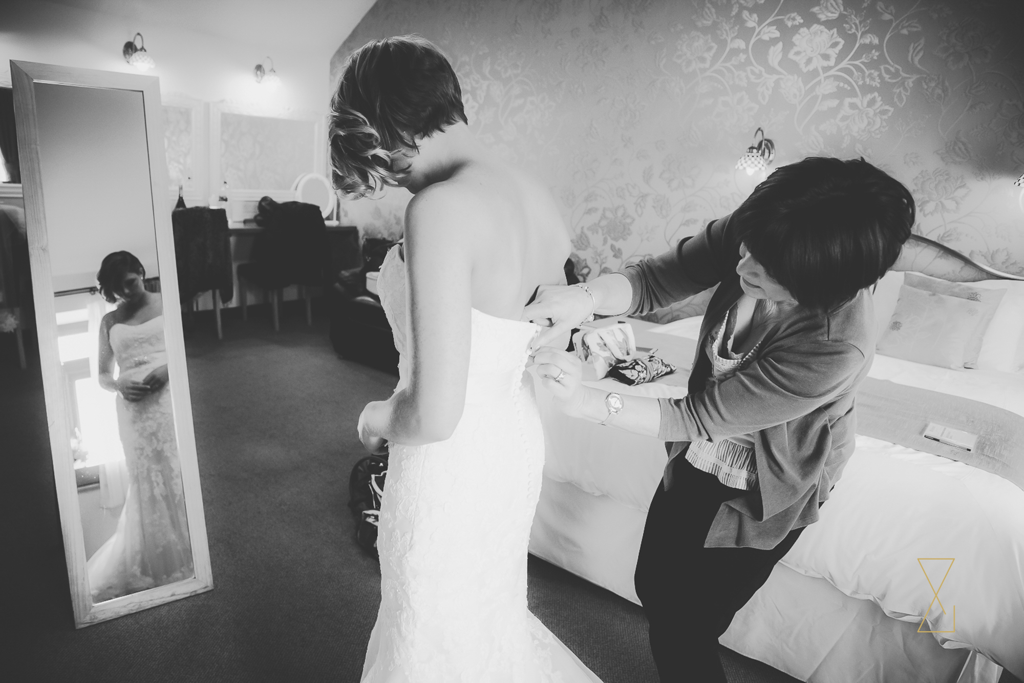 Mother of the bride buttoning the wedding dress at Heaton House Farm, Evans & Evans wedding photography