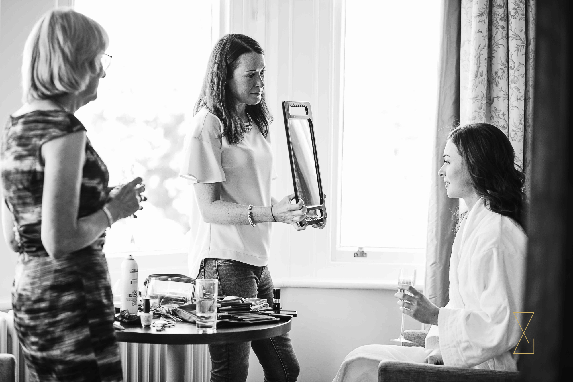 Bride checks her reflection at Laura Ashley Belsfield, Evans & Evans wedding photography