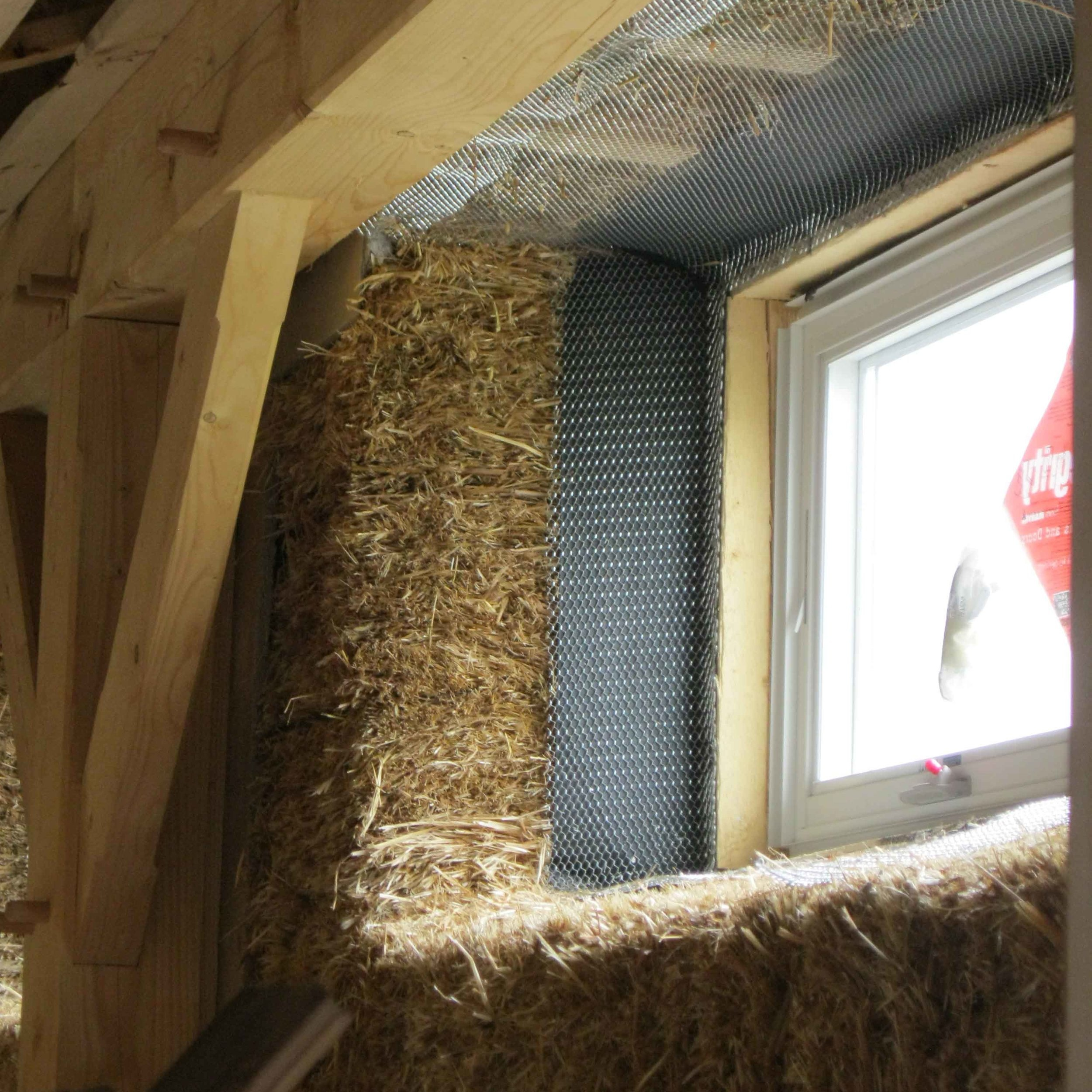 Detail showing exterior wall under construction with straw-bale and post and beam wood frame.