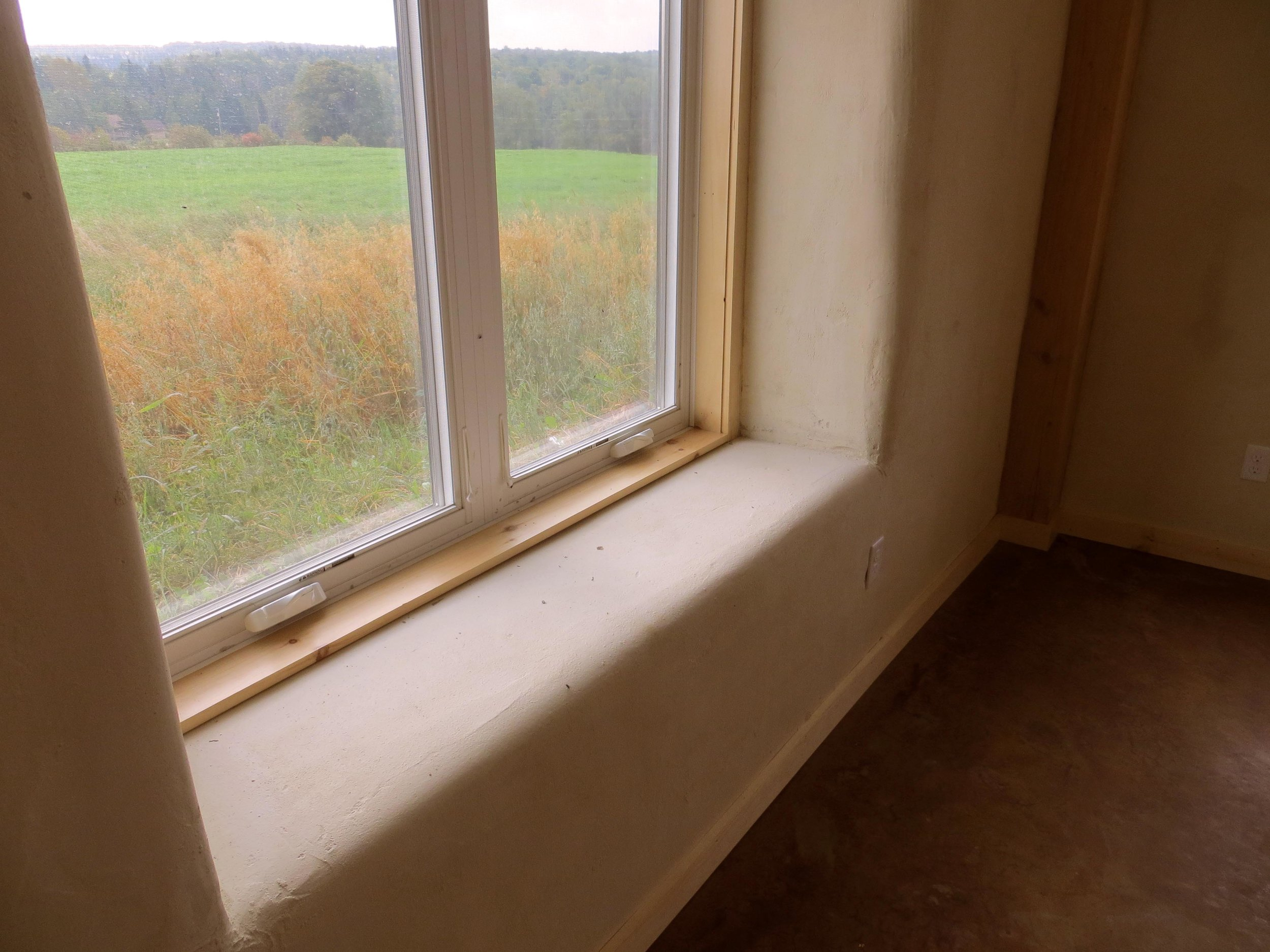 The rounded edge of the window sill belies the presence of straw-bales below