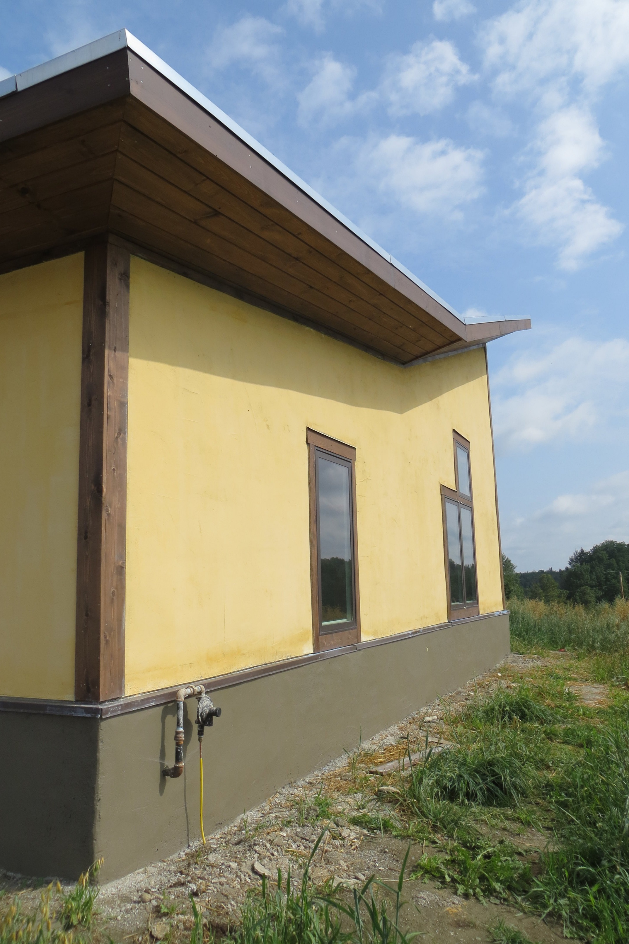 Exterior view of building corner and uplifting roof along with flared straw-bale wall with its exterior plaster.