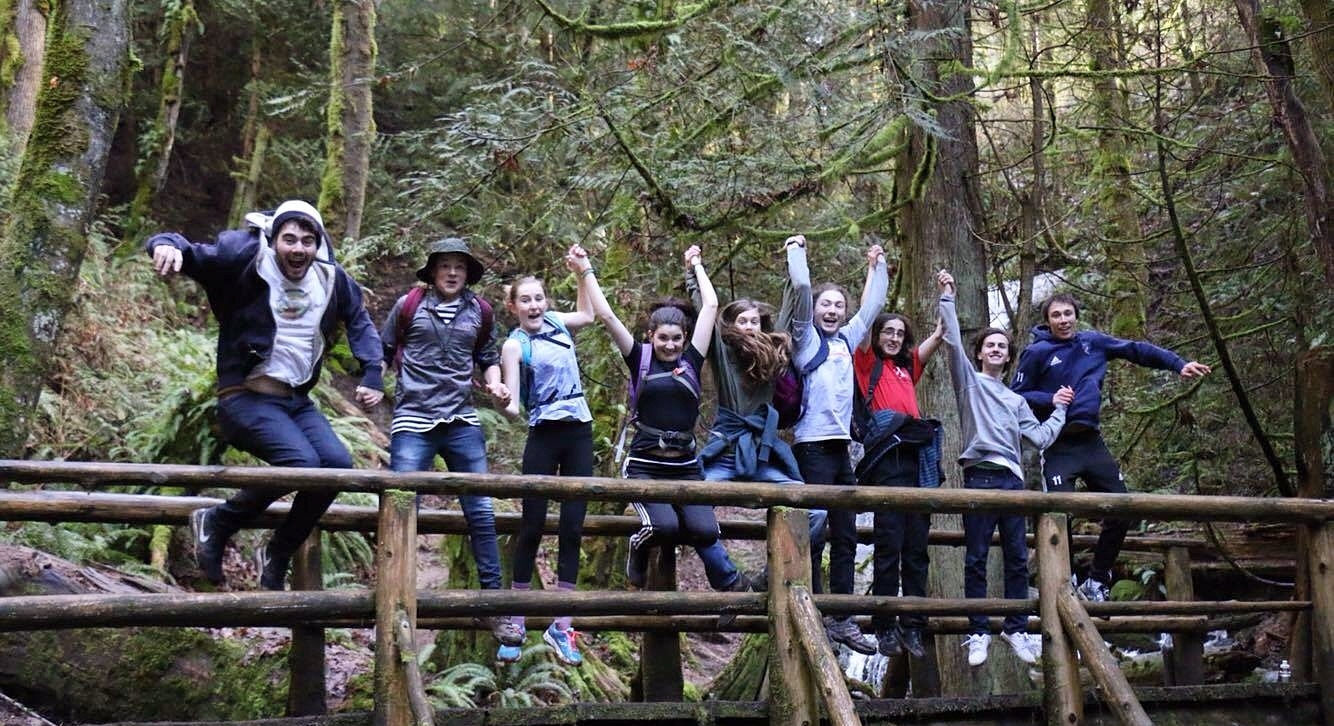 A group of teenage students on a hike, jumping for joy on a bridge.