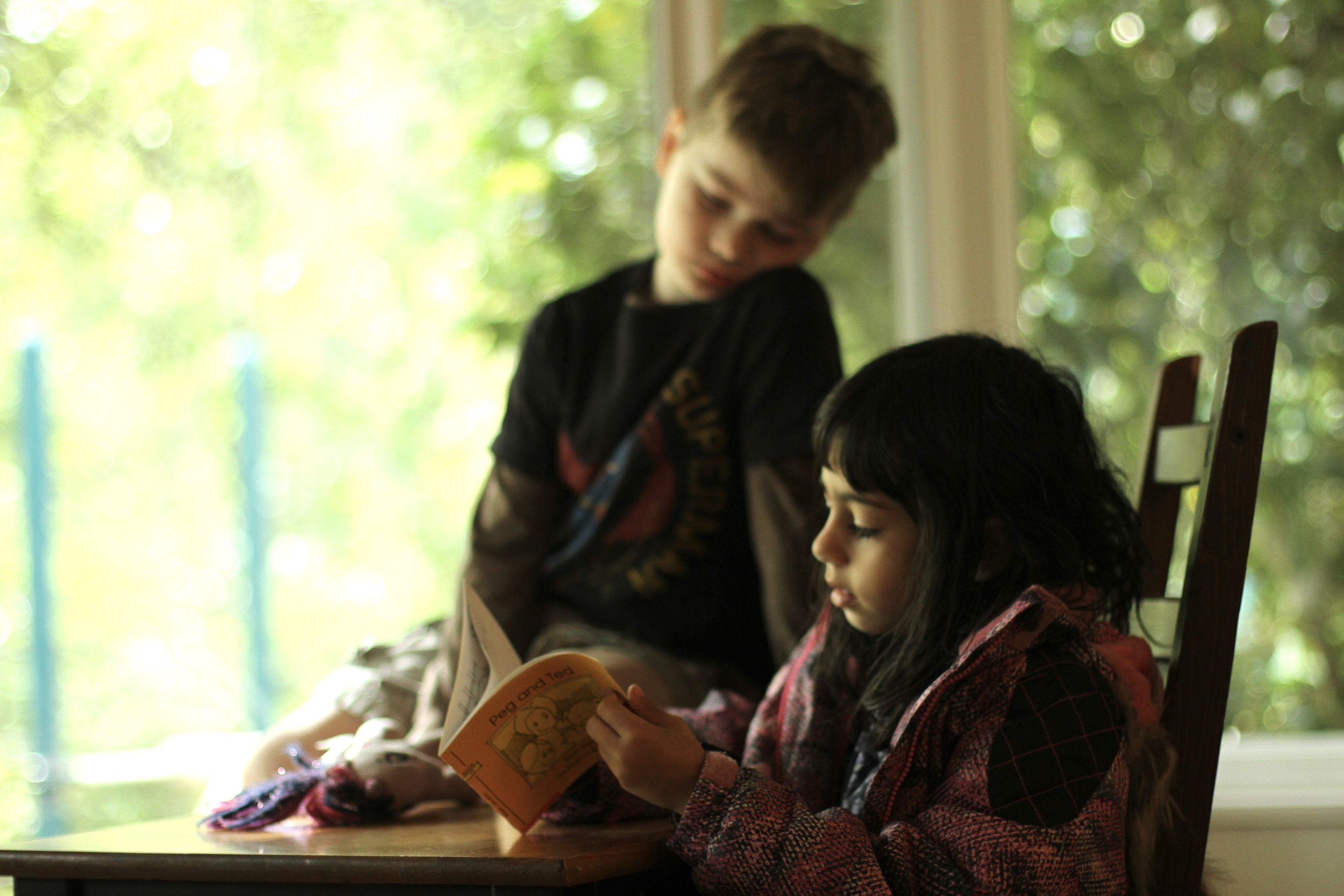 Two young students reading a book together.