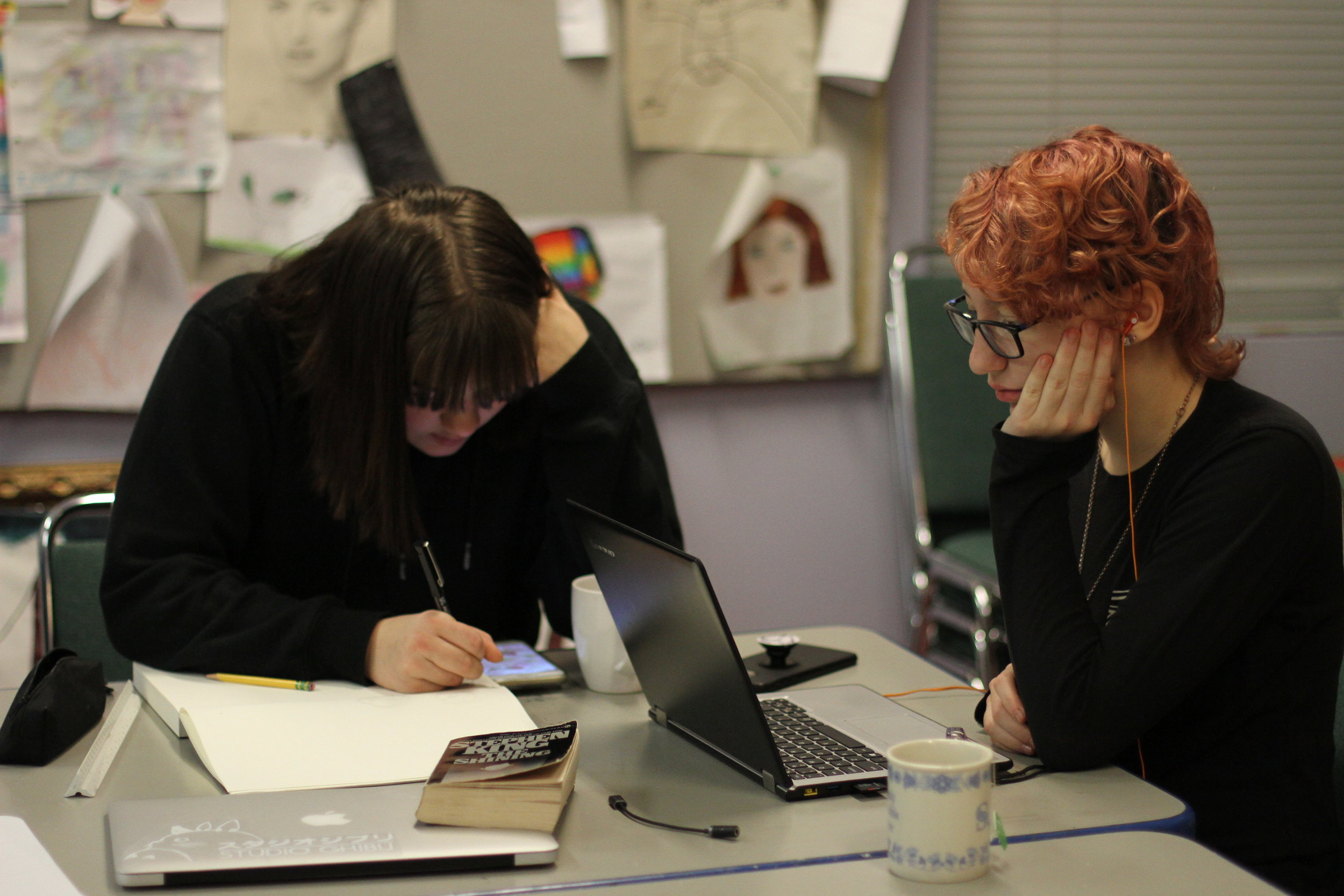 Two students drawing and studying in the art room.