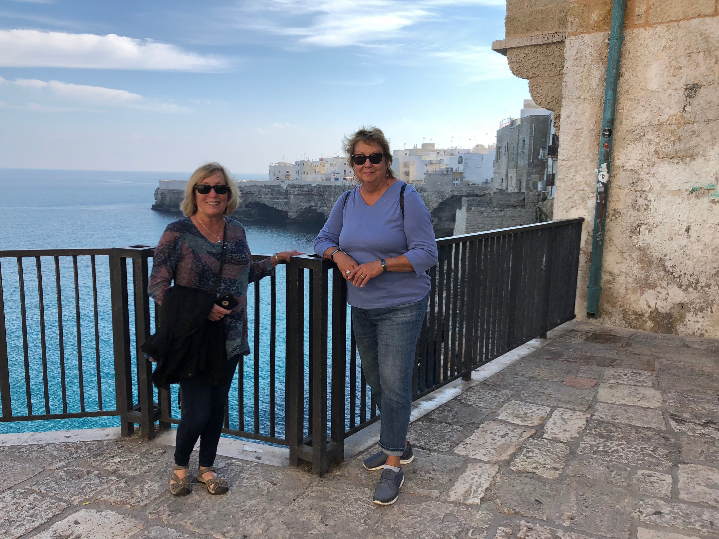 travelers betsy & kathy enjoy the sea views from the streets of polignano a mare in puglia