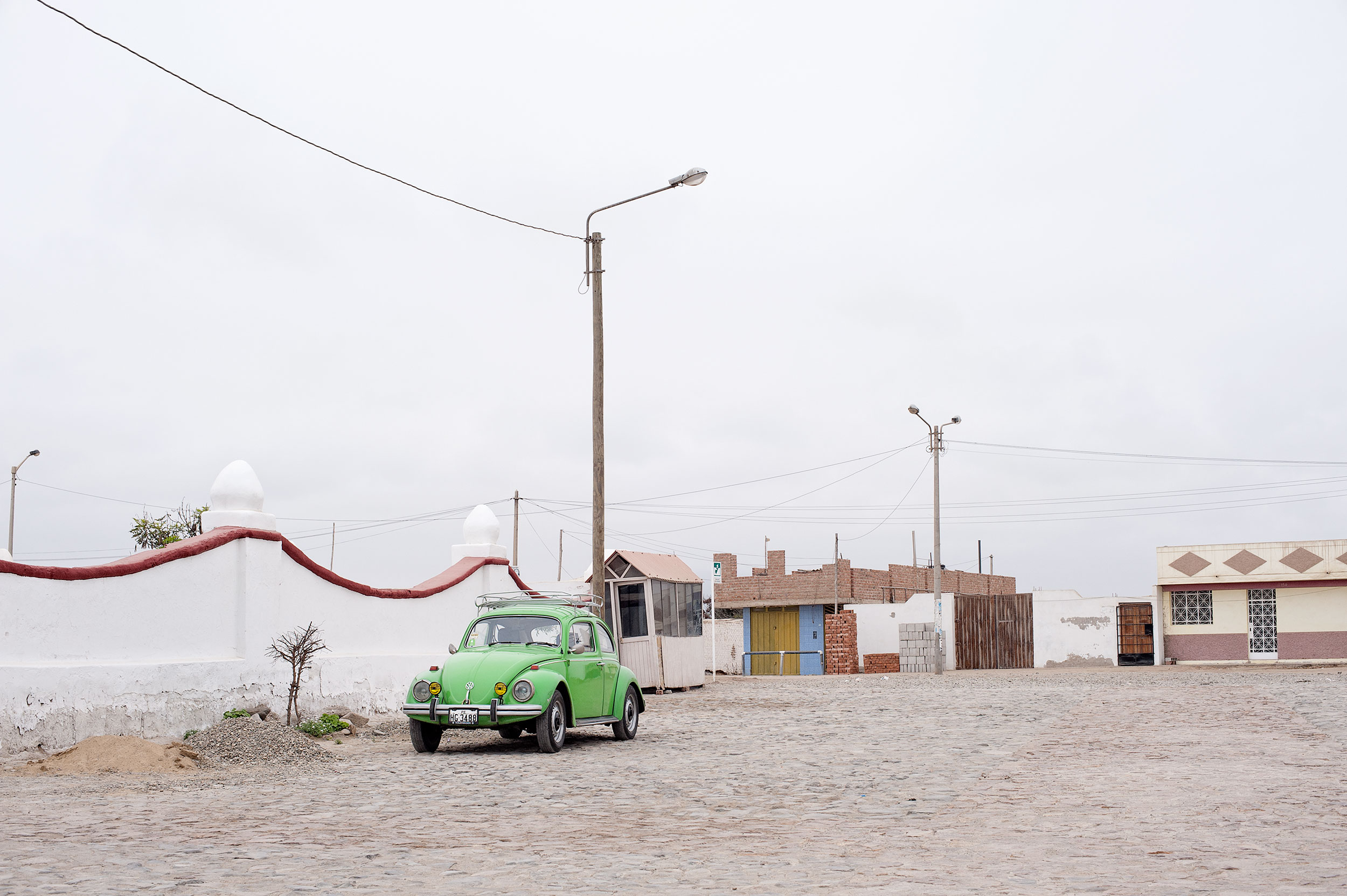 One of the most popular cars in Peru Volkswagen Beetle parked outside cemetery in Huanchaco.