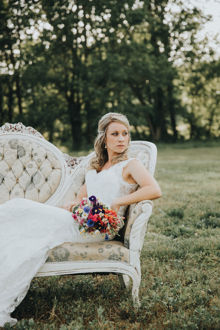 vintage inspired bridal session on tufted loveseat in open field at north carolina barn