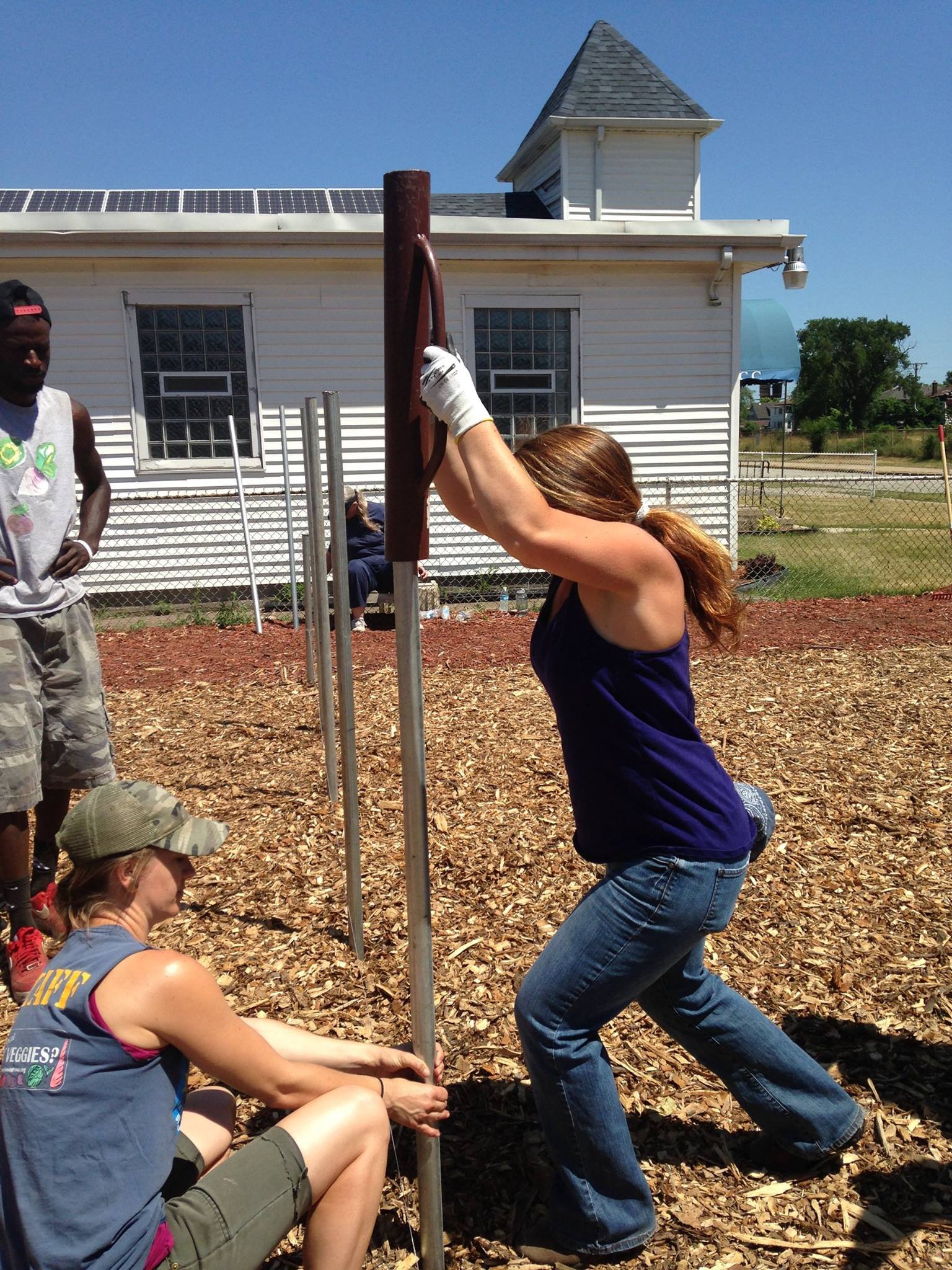 Council board member Anne McShane-Massie drives posts with help from Growing Power staff