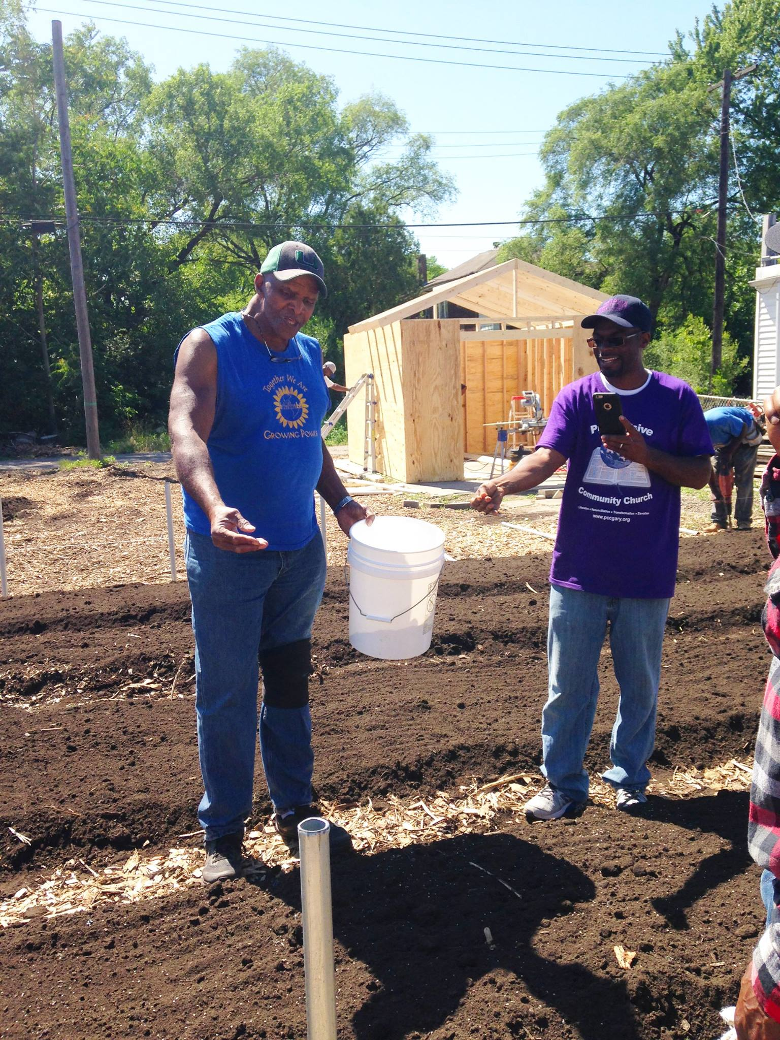 Will Allen demonstrates hand-sowing seeds with Pastor Curtis Whittaker