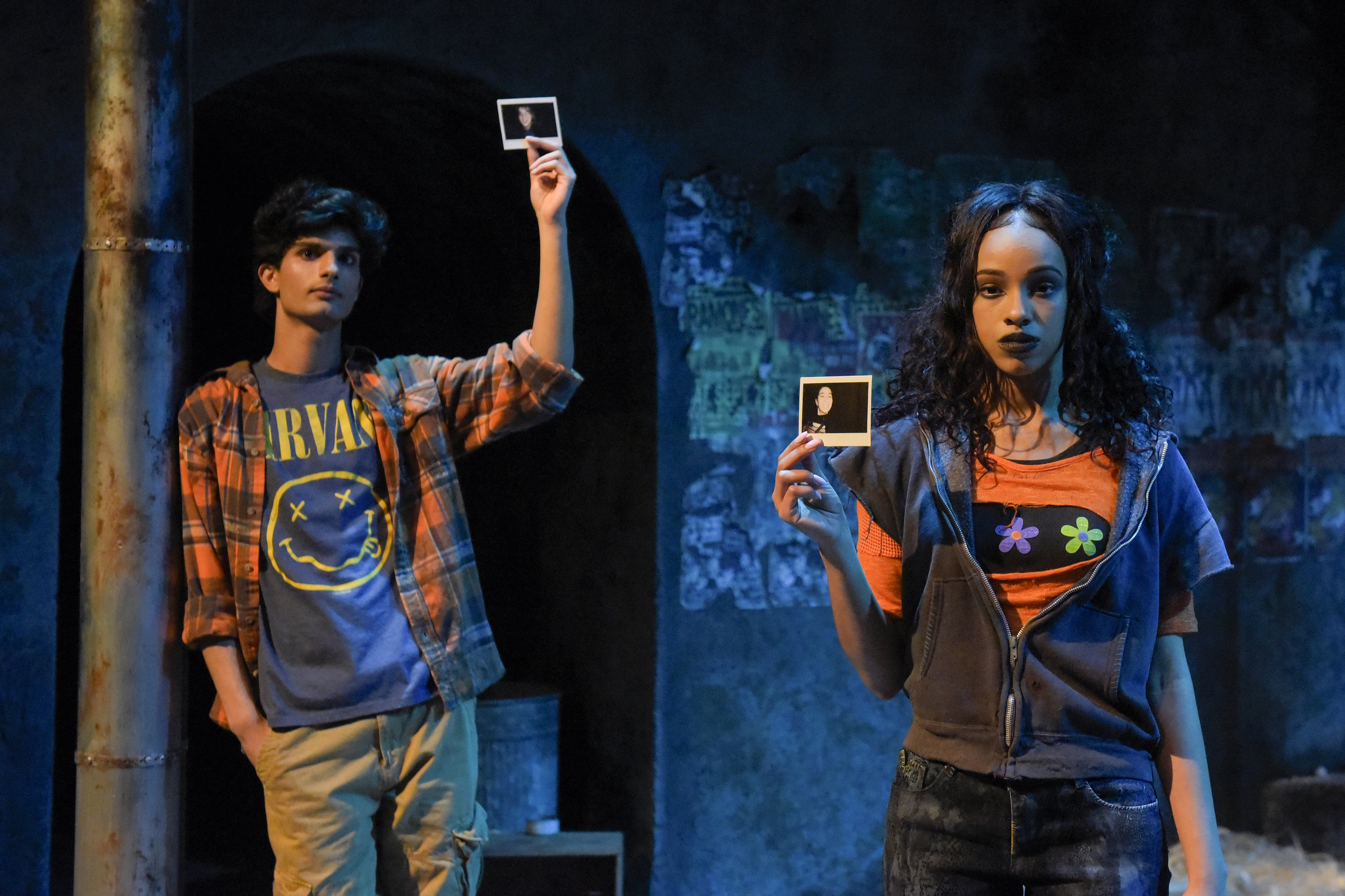 Orpheus (Yohana Ansari-Thomas) and an ensemble cast member (Farryl Lawon) hold up photographs of some of the real street youth whose interviews with playwright Naomi Iizuka inspired  Polaroid Stories . Photo: Alessandra Mello.