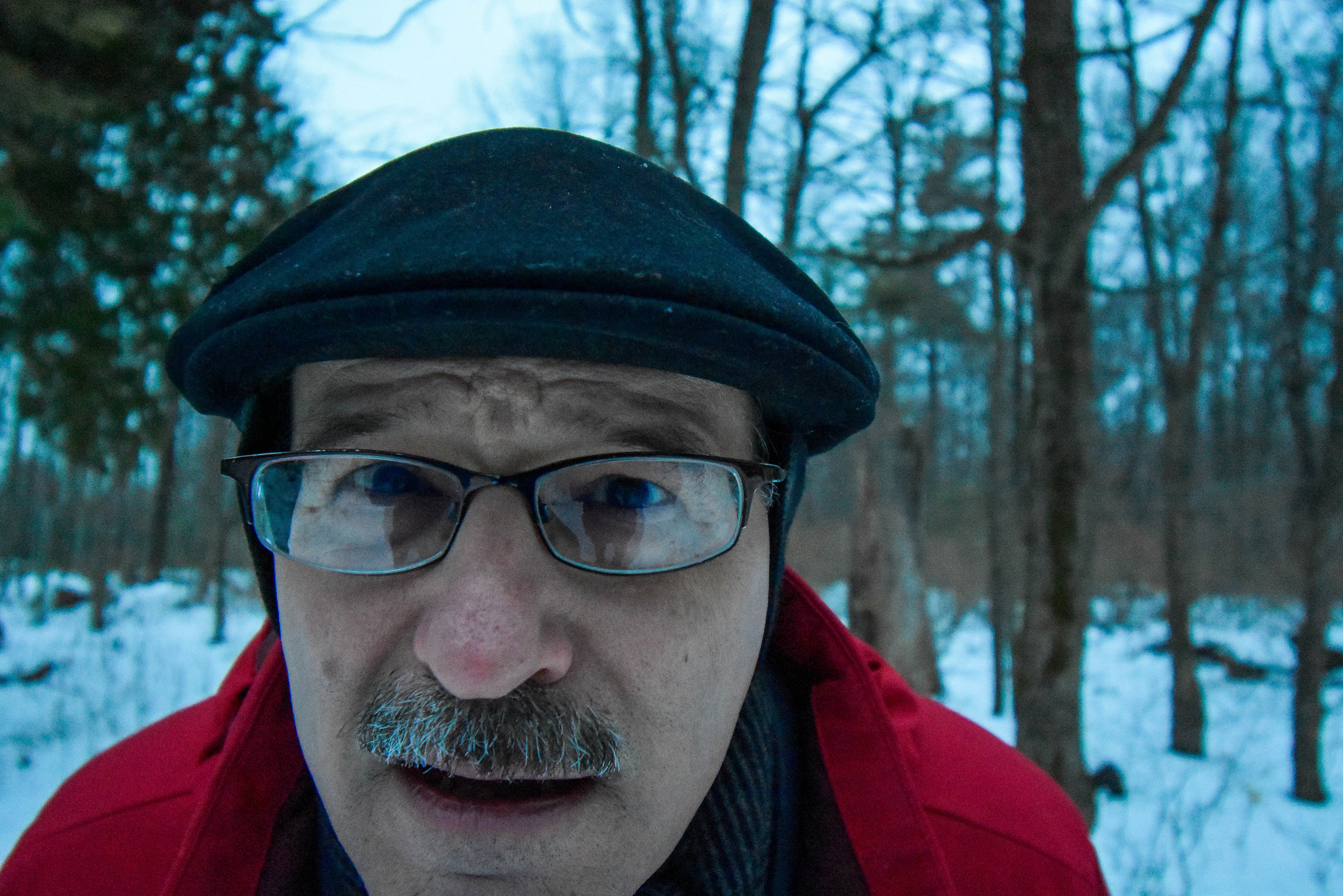 During a family hike, my father stops to check my lens for debris, caught off guard when I decided to photograph him.