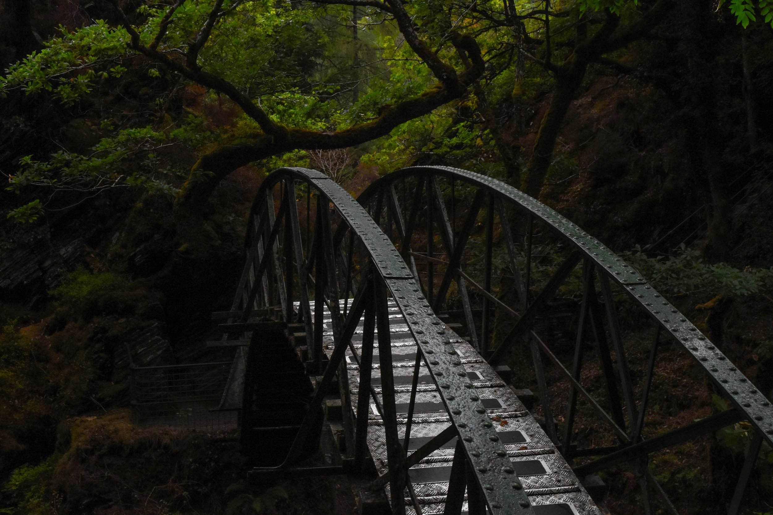 A metal footbridge spans the Afon Mynach river along the Devils Bridge Nature Trail in Ceredigion, Wales.