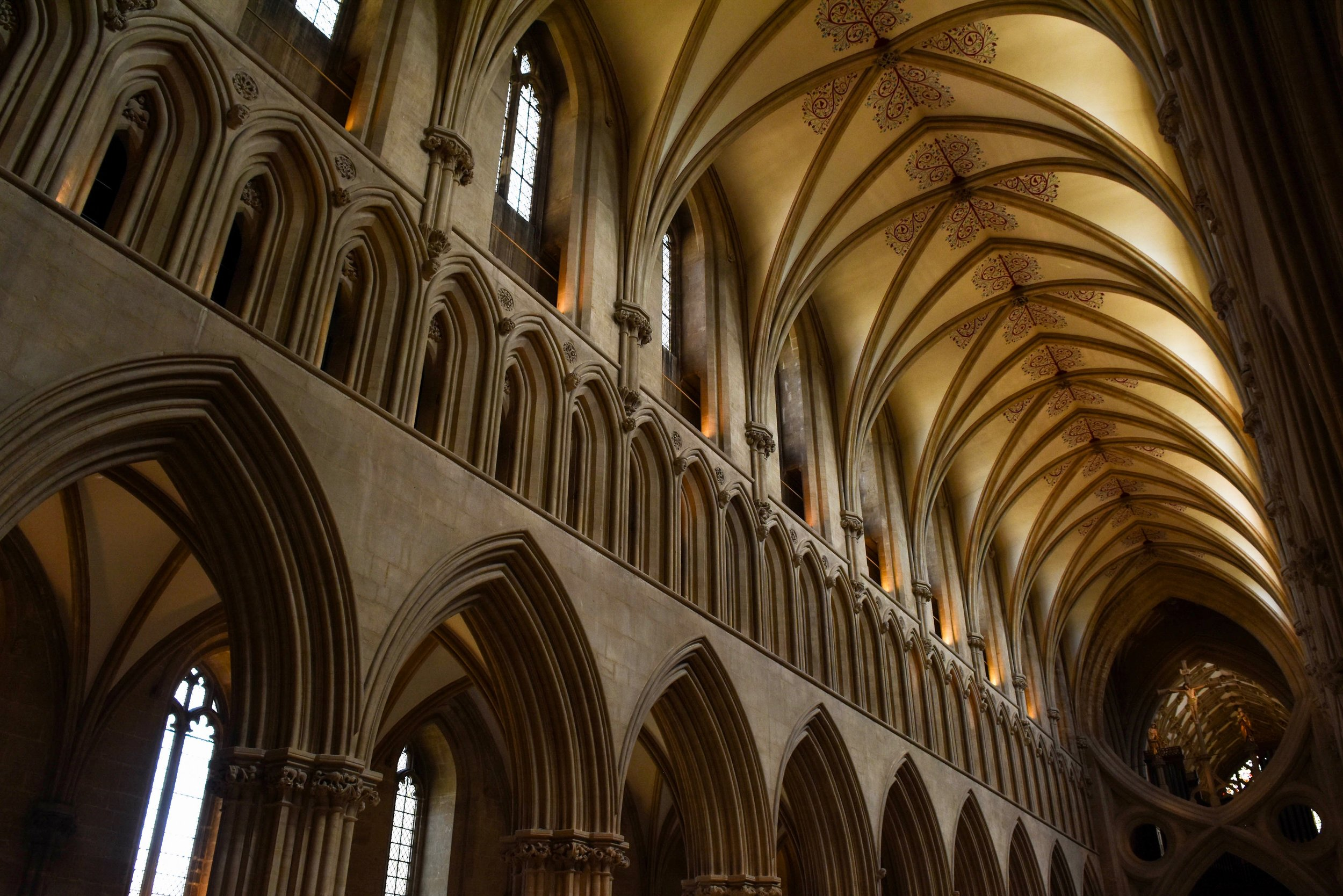 Wells Cathedral in Somerset, England, features vaulted ceilings and a distinctive structure of scissor-like supporting arches, seen in the photo's lower right corner.