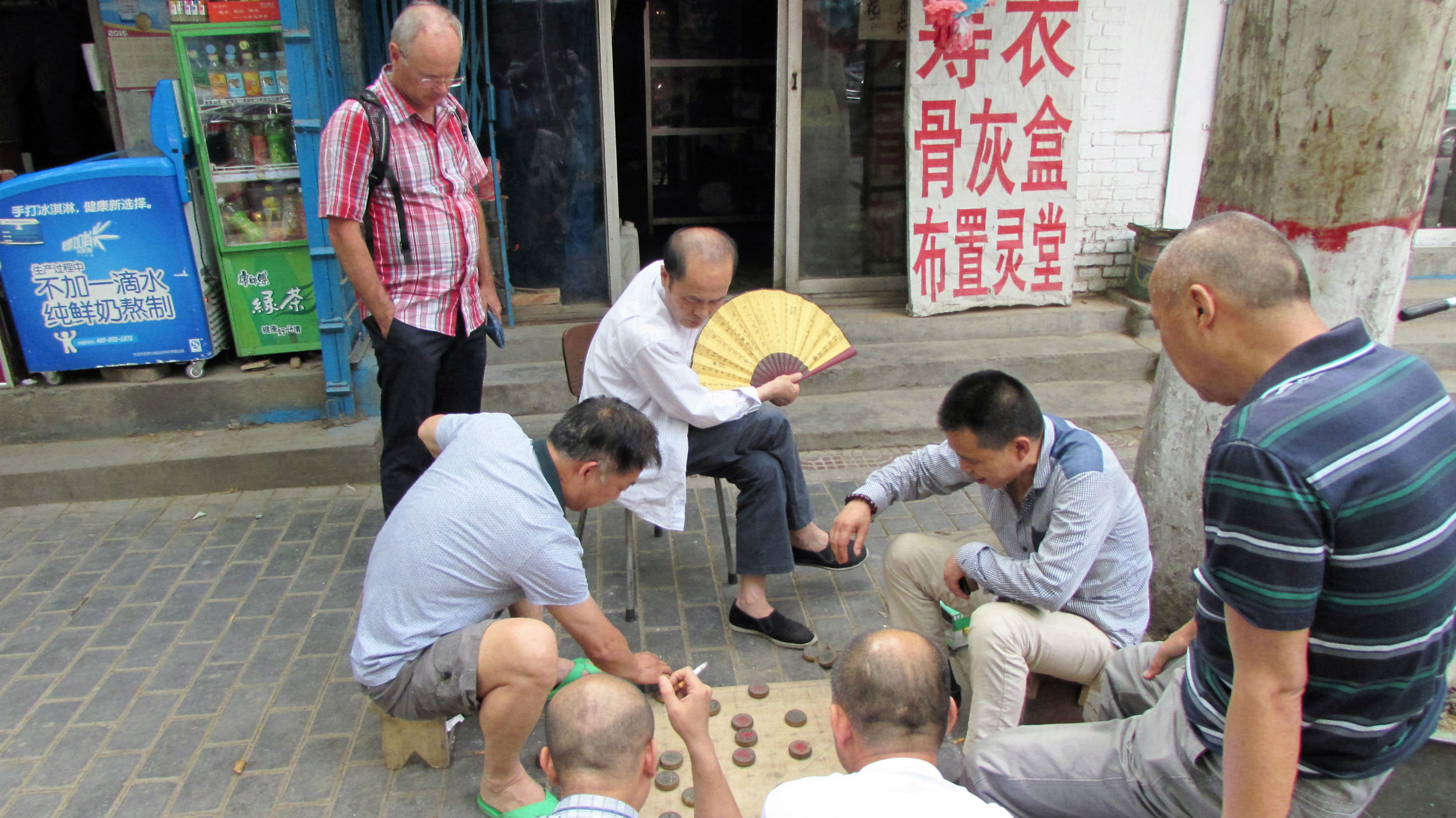 Playing xiangqi (chinese chess) in the streets of Xi'an. Spectators will loudly give advice to the players and criticize moves.