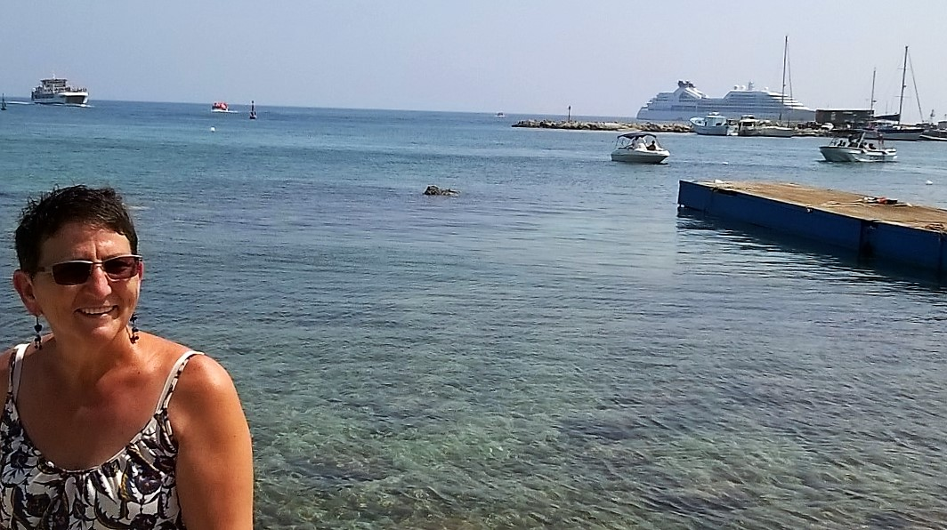 Francien in the historic harbour of Paphos. The harbour arm has a Roman breakwater sunk under the water. A cruiseship anchored offshore.