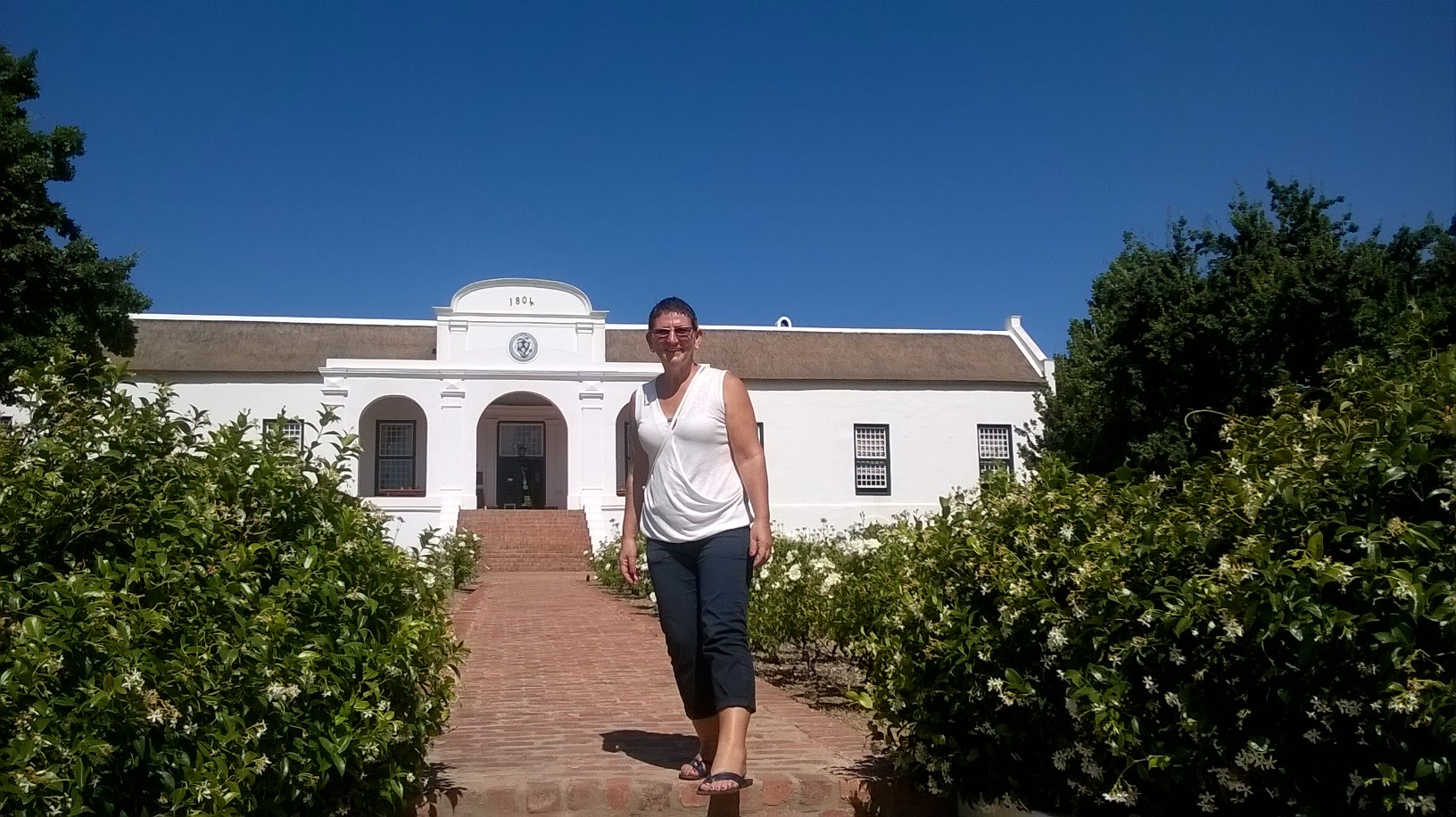 Francien in front of Cape Dutch manor house at a wine estate