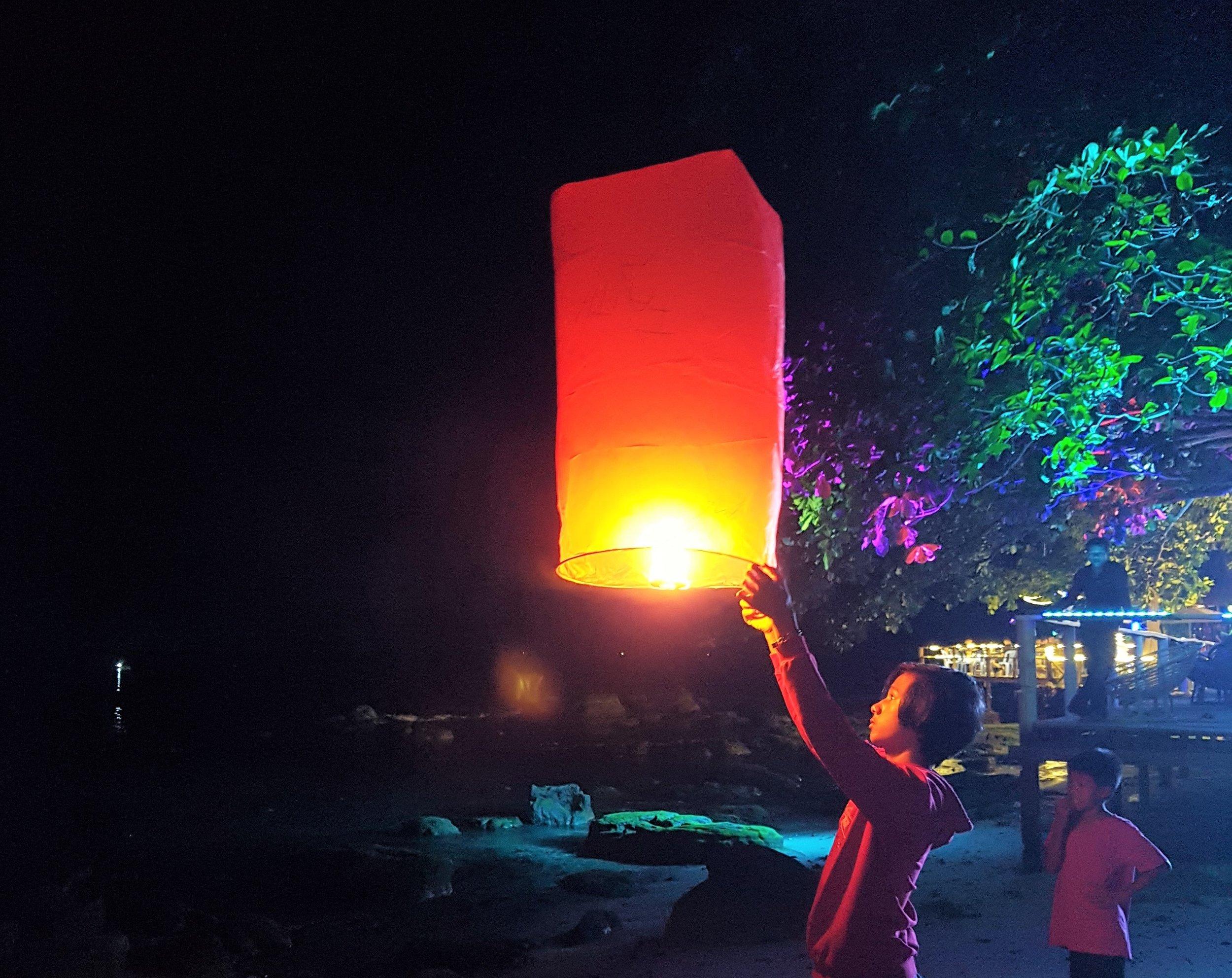 Local boy launching a Chinese flying lantern