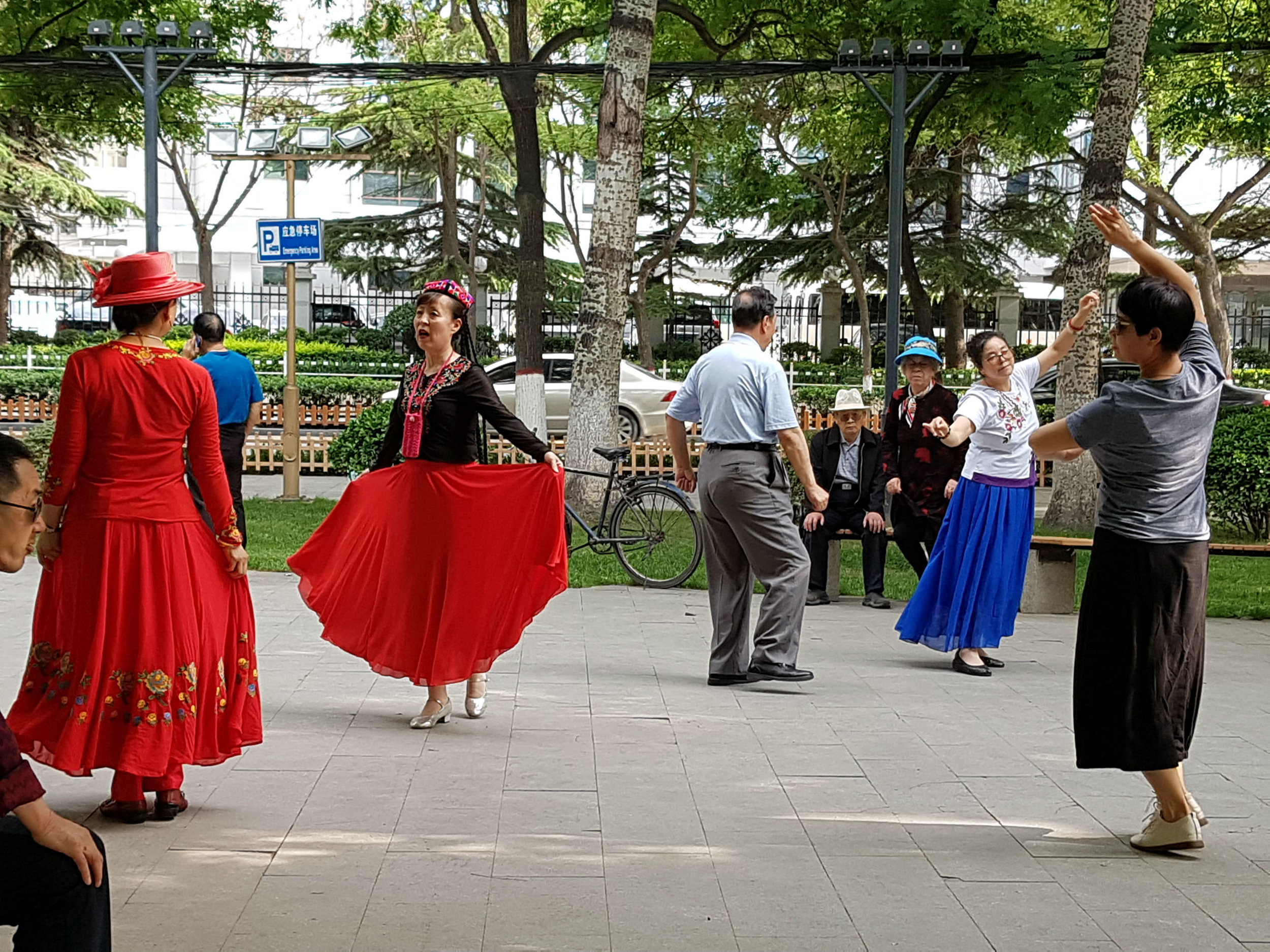 People singing and dancing in a park in Beijing
