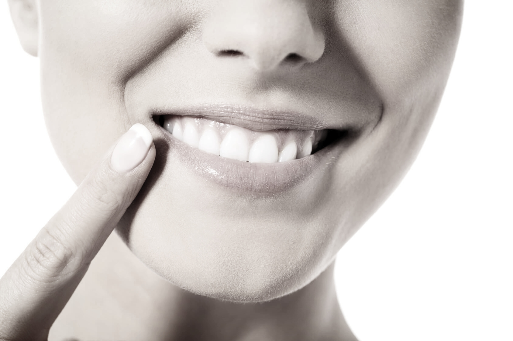 Close-up of patient pointing to their beautiful straight teeth after braces