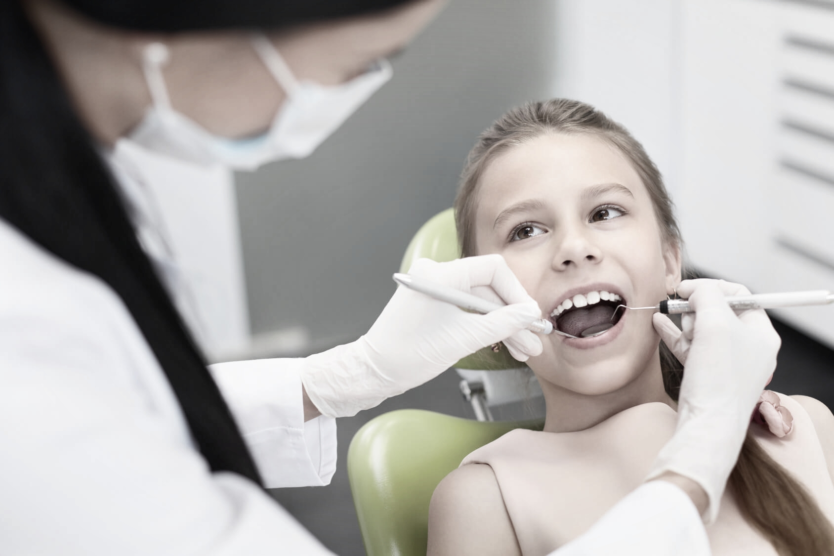 Girl smiling in the dentist chair as she has her regular child dental check-up