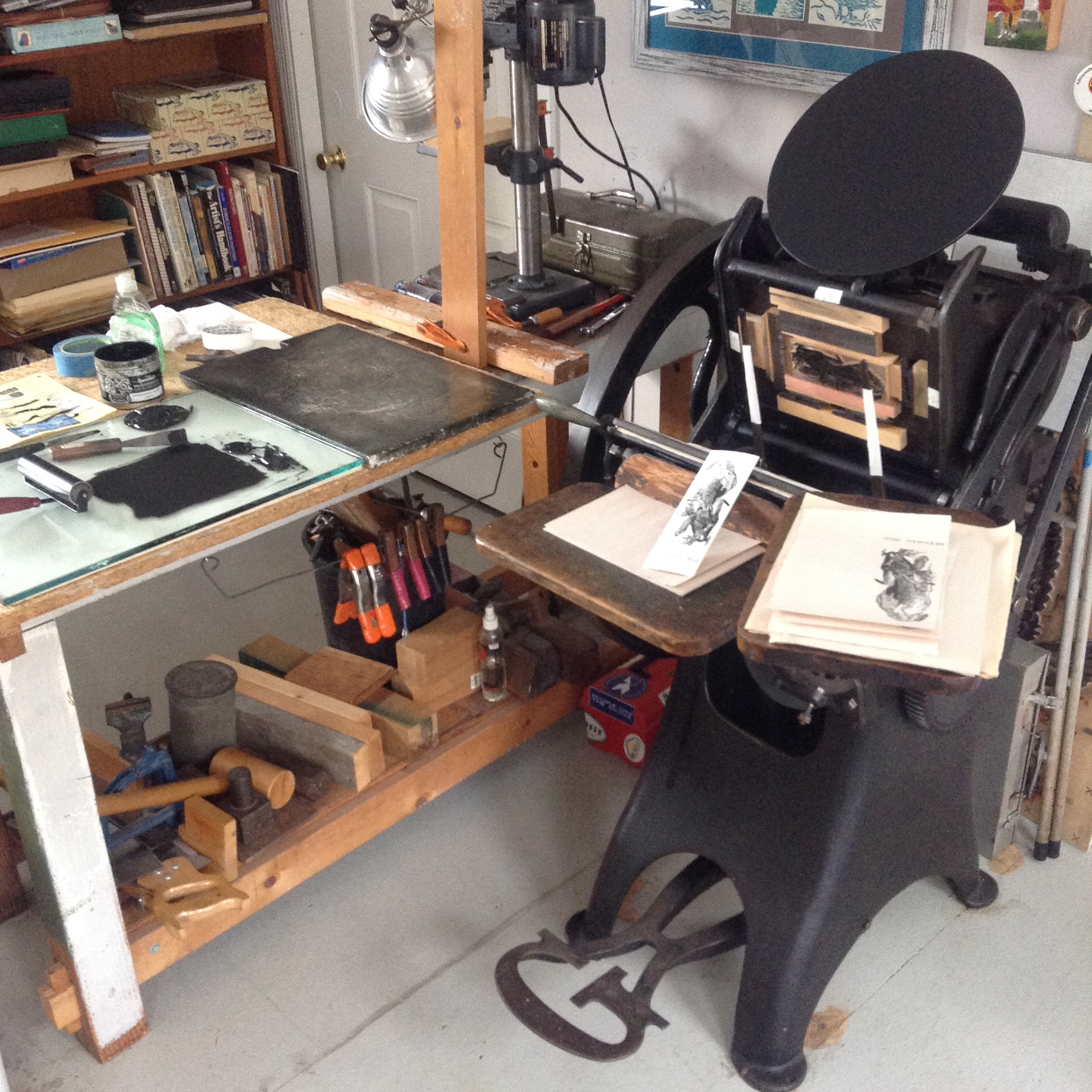 Chase is placed into the press and printing can begin. Ink slab and ink is seen on workbench to the left