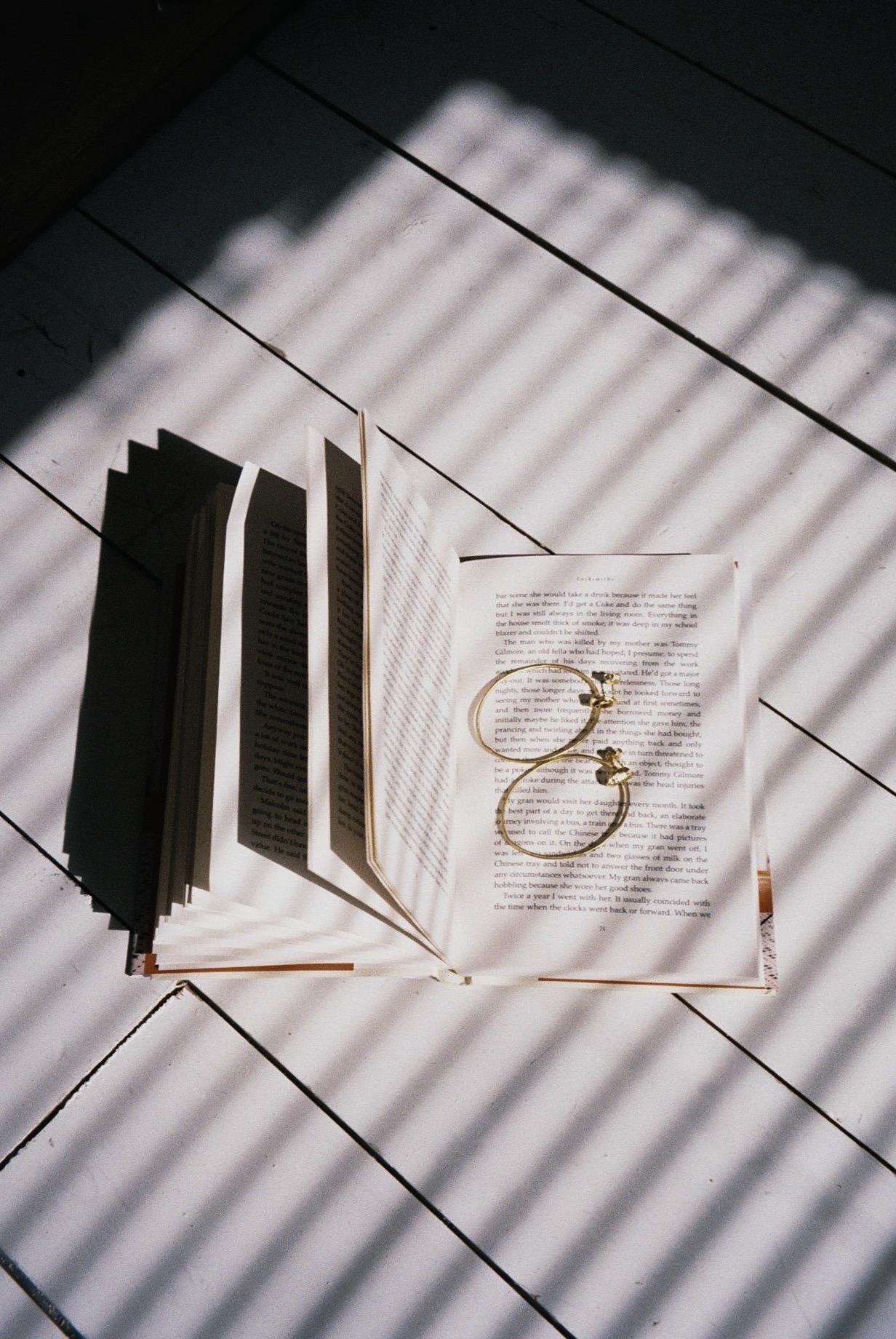 "A short-stories book which I stopped reading half way throw and the beautiful    ""Mira"" hoops    designer by Juliana Bezzera.  / Um livro de short-stories que deixei a meio e os  brincos  maravilhosos a que a designer, Juliana Bezerra, intitulou de ""Mira""."