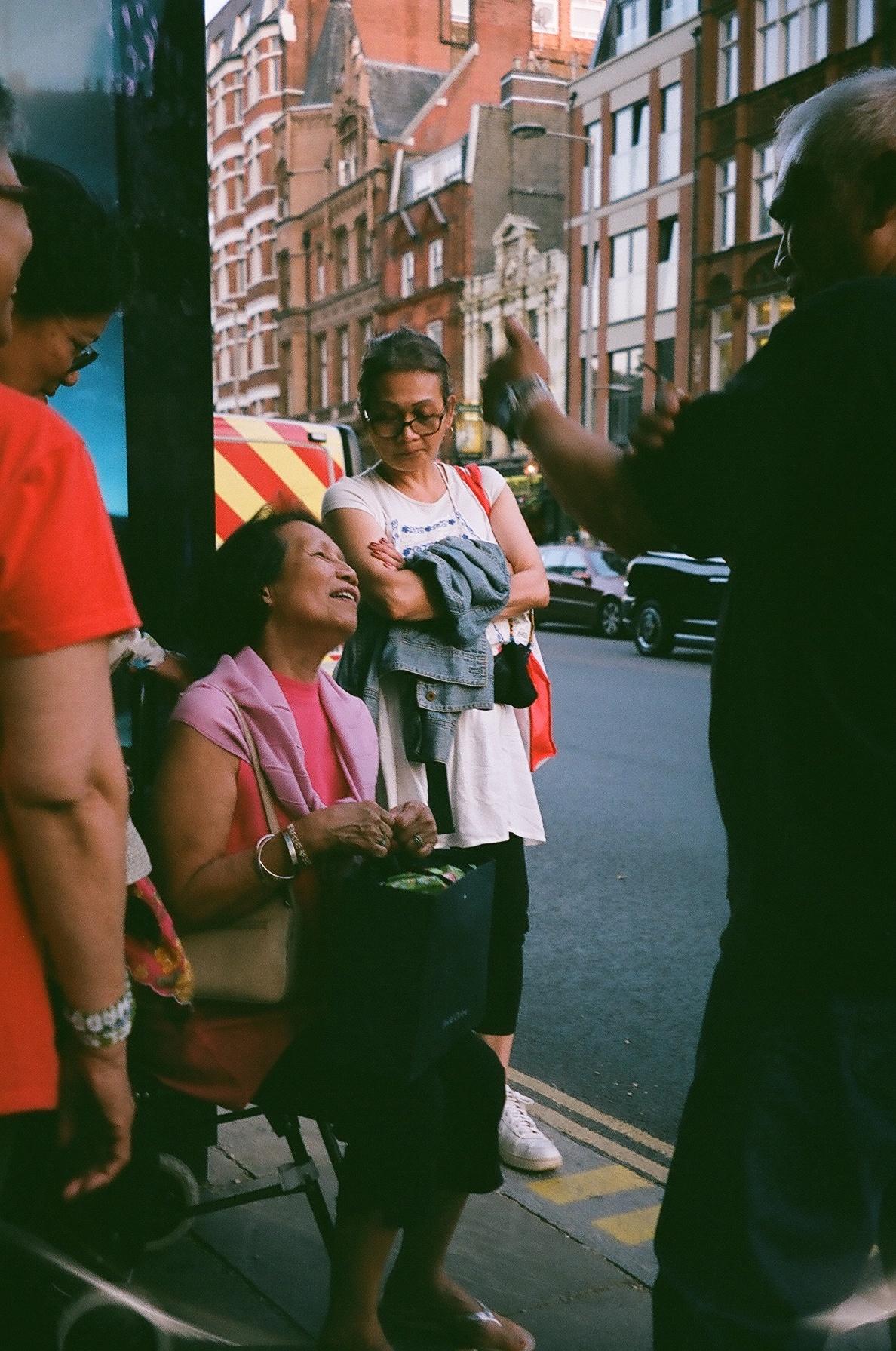 """Londoners at a bus stop. The lady, realising that I was taking a photograph of her, smiled and asked to see it. When I told her it was a film camera she said, """"I hope I look beautiful."""" She does.  / Londoners numa paragem de autocarro. A senhora, apercebendo-se de que lhe tirava uma fotografia, sorriu e pediu para a ver. Quando lhe disse que a máquina era analógica disse """"espero que eu tenha ficado bonita"""". E ficou :)"""