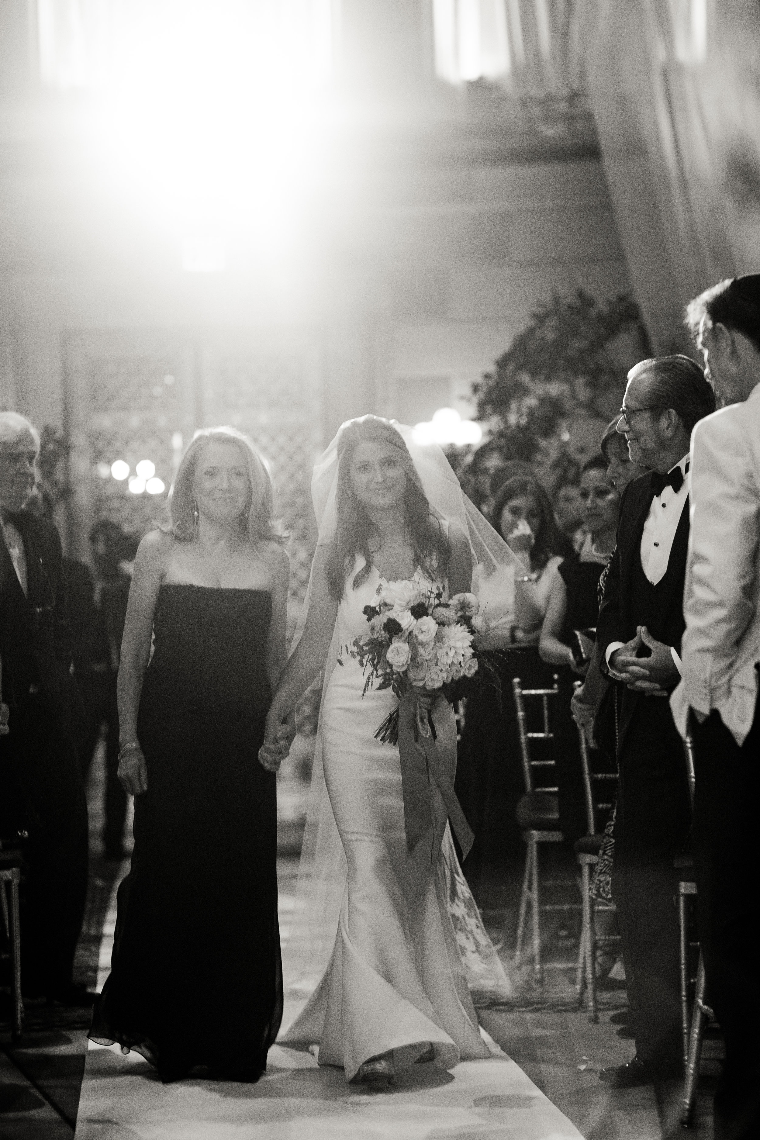 Alix's mother walking her down the aisle during her ceremony.