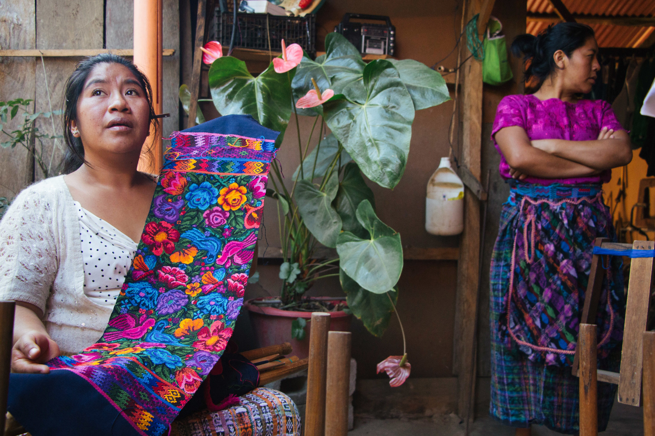 LEIDY AMARILIS MARTINEZ SHOWCASES ONE HER HANDMADE TEXTILES WHILE ESMIDA MAIDE MARTINEZ WATCHES HER MOTHER WEAVE IN THEIR HOME IN SAN ANTONIO AGUAS CALIENTES, GUATEMALA ON JAN. 9. SAN ANTONIO IS KNOWN FOR HUIPILES WOVEN ON BOTH SIDES.