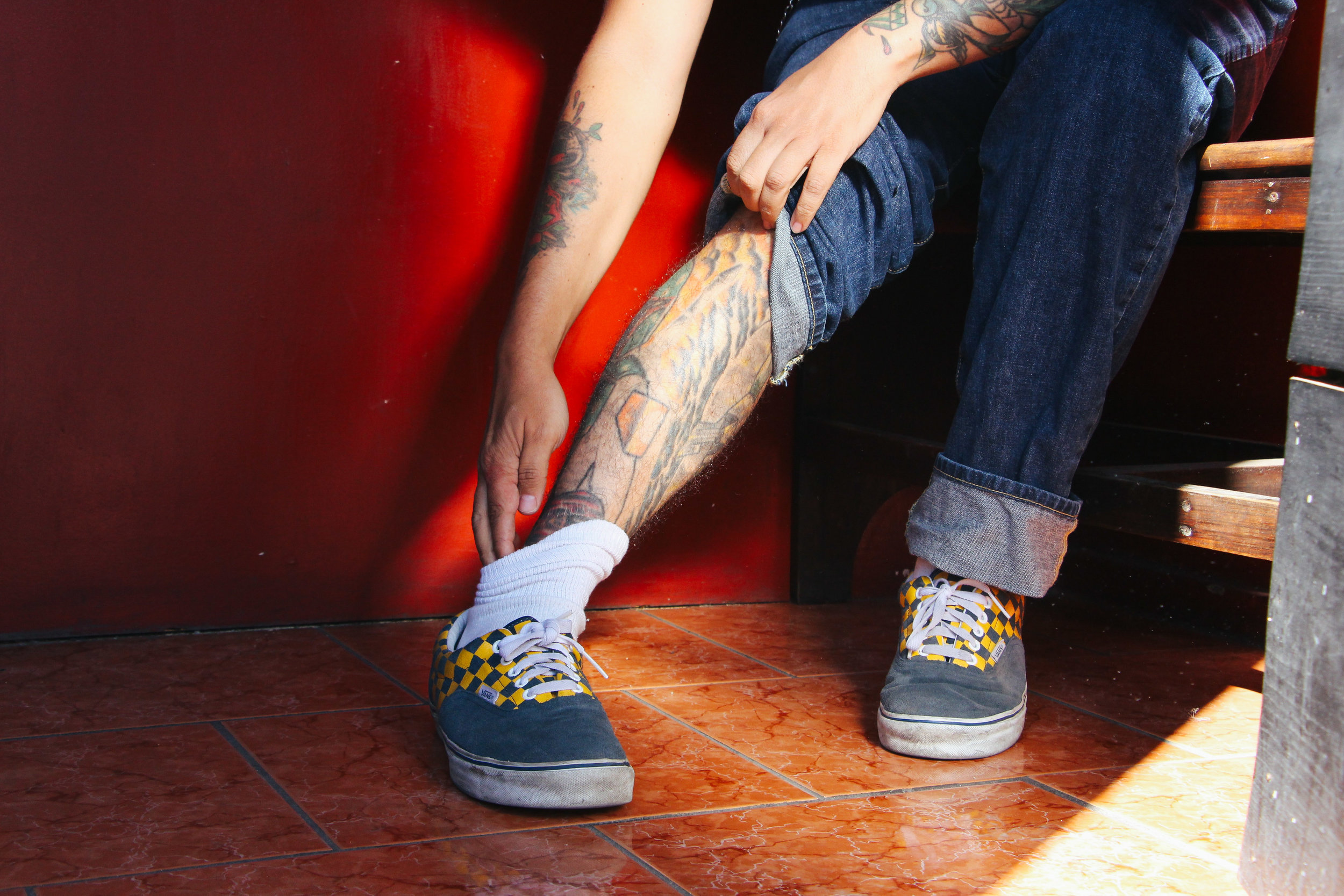 Photo by Kendall Soderstrom TATTOO ARTIST CARLOS WOLFOS ROLLS HIS JEANS TO EXPOSE HIS COLLECTION OF TATTOOS IN THE SMALL LOBBY OF ANTIGUA TATTOO IN ANTIGUA, GUATEMALA ON JAN. 13. HIS FIRST TATTOO OF A WOLF DISPLAYS ITSELF ON HIS RIGHT SHOULDER.