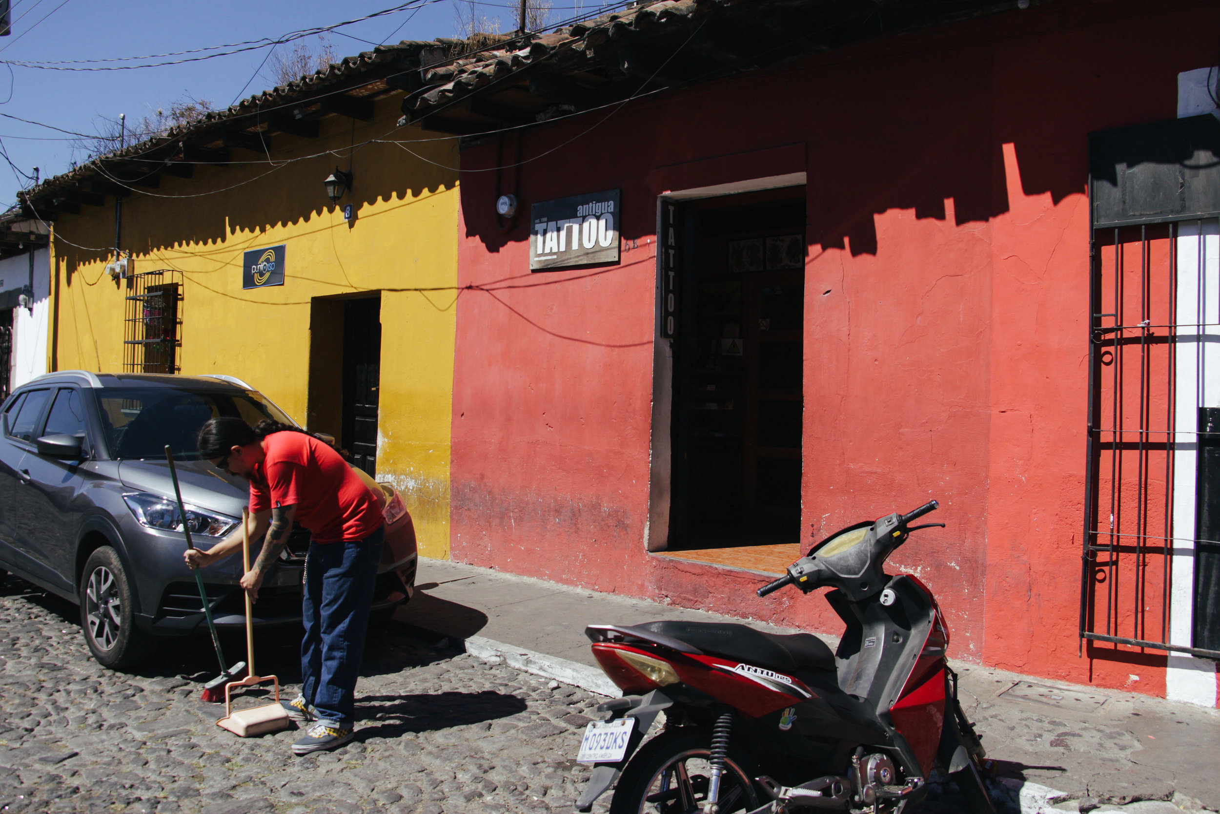 Photo by Miranda Weippert TATTOO ARTIST CARLOS WOLFOS SWEEPS THE COBBLESTONE STREET OUTSIDE OF HIS BROTHER LUIS BEDREGAL'S TATTOO SHOP IN ANTIGUA, GUATEMALA ON JAN. 13. WOLFOS HAS WORKED WITH HIS BROTHER SINCE 1998.