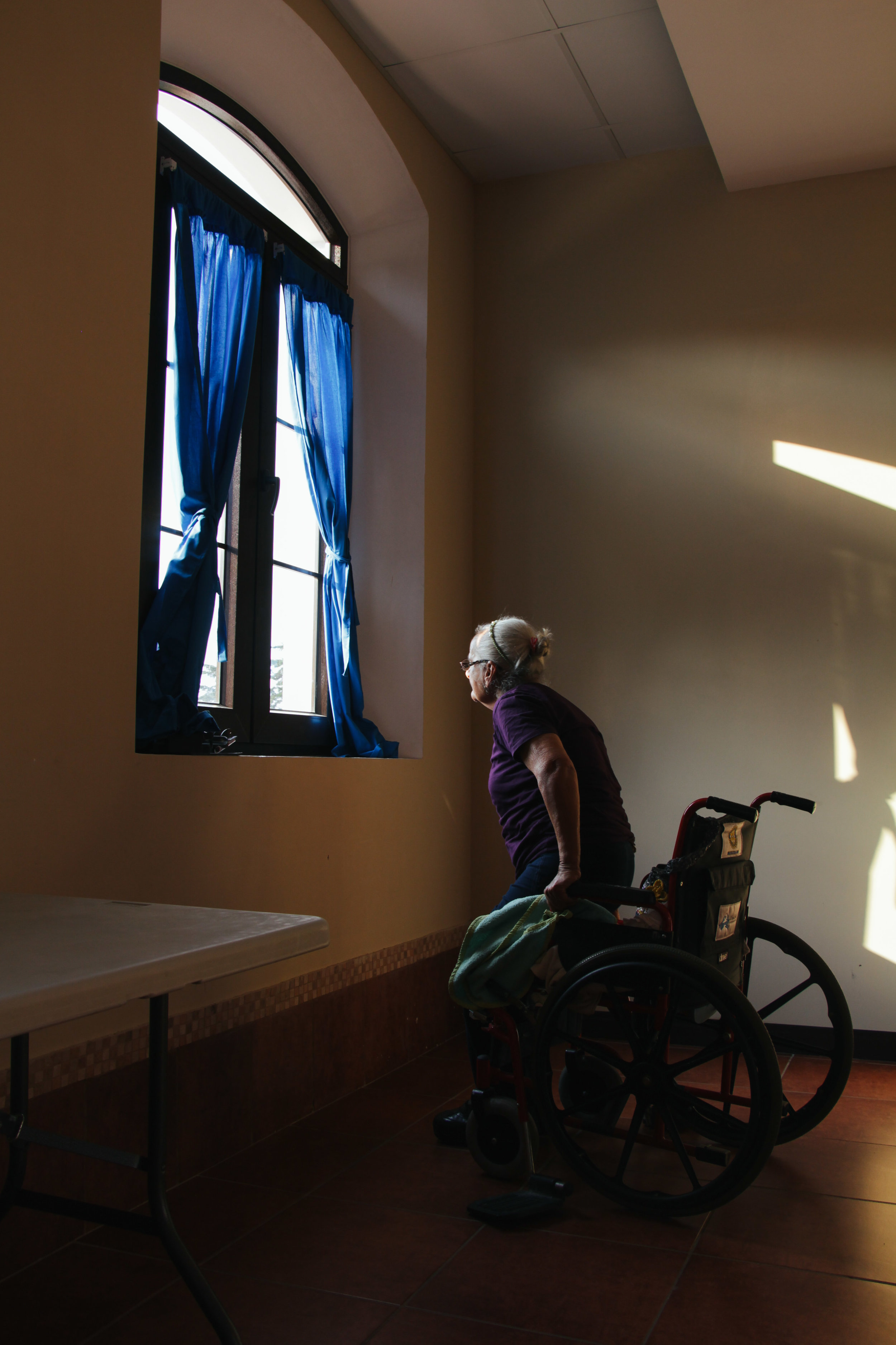 Photo by McKenzie Van Loh GLADYS SEGURA, 75, LIFTS HERSELF OUT OF HER WHEELCHAIR TO TAKE A LOOK OUT THE WINDOW AT VIRGEN DEL SOCORRO IN ANTIGUA GUATEMALA JAN. 17. VIRGEN DEL SOCCORRO'S NEW BUILDING IS SURROUNDED BY VOLCANOES