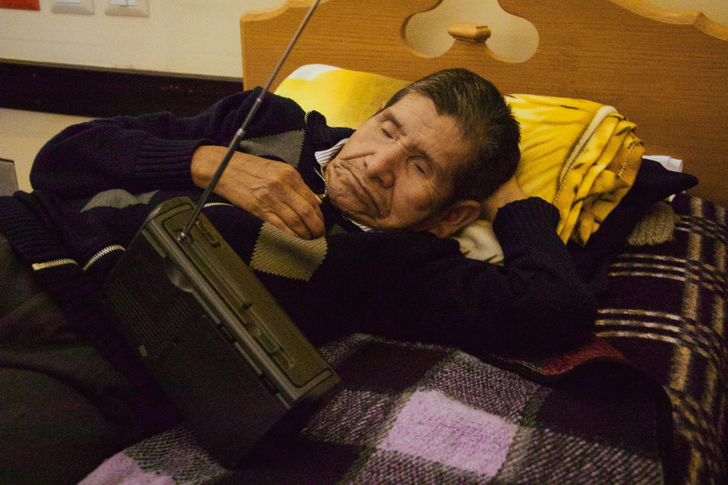Photo by Miranda Weippert ANTONIO RAMÍREZ, 67, LAYS PEACEFULLY ON HIS PLAID SHEETS WITH HIS HANDHELD RADIO AT HIS SIDE AT VIRGEN DEL SOCCORRO JAN. 17. HE ENJOYS LISTENING TO NEWS WHILE HE TRIES TO SLEEP.