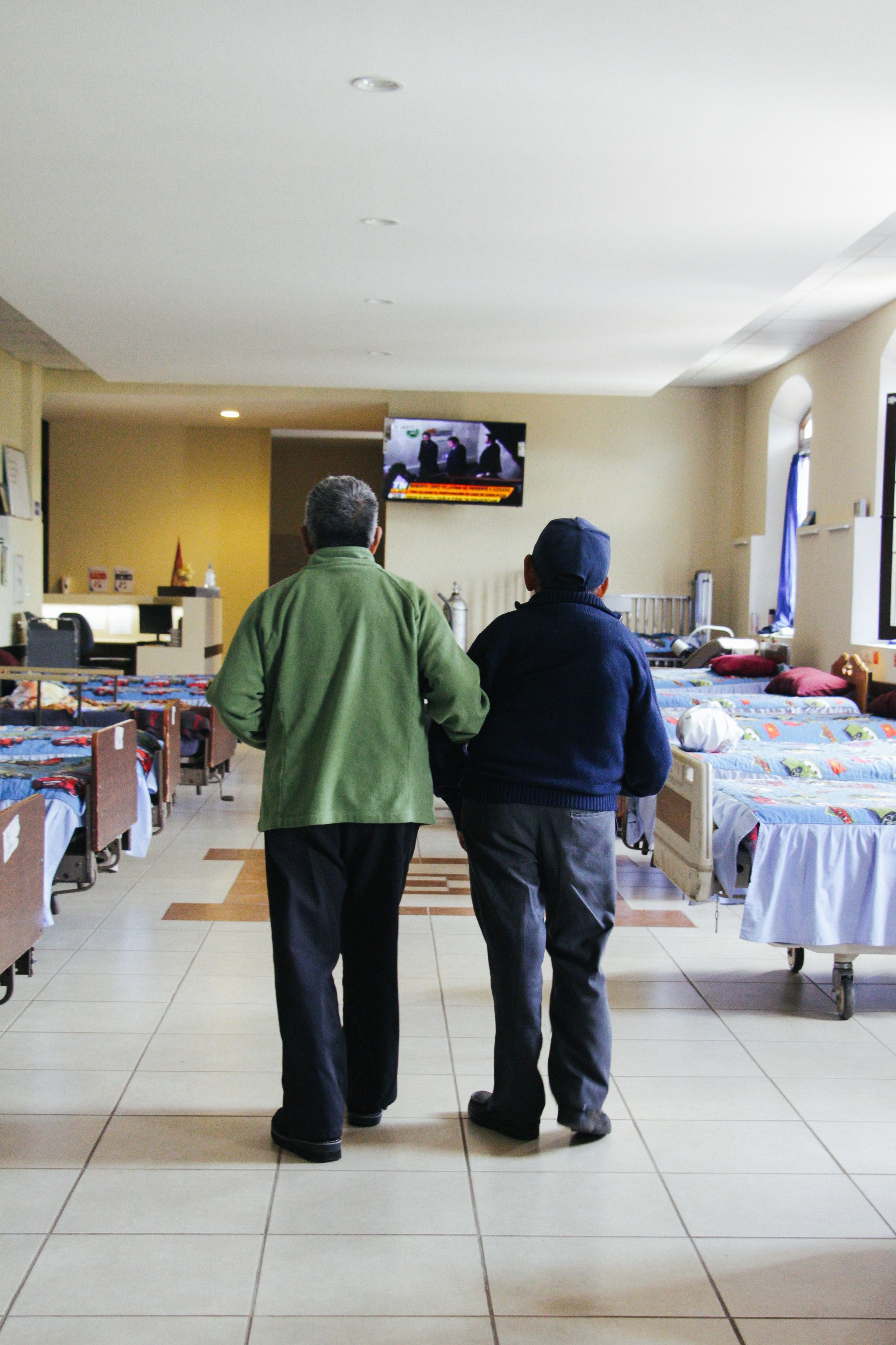 Photo by Isabela Sagastuy CATARINO PEREZ HELPS ANTONIO RAMÍREZ WALK BACK TO HIS BED AFTER EATING LUNCH AT VIRGEN DEL SOCORRO ON JAN. 16. PEREZ AND RAMIREZ MET IN ANTIGUA AND HAVE BEEN GOOD FRIENDS EVER SINCE.