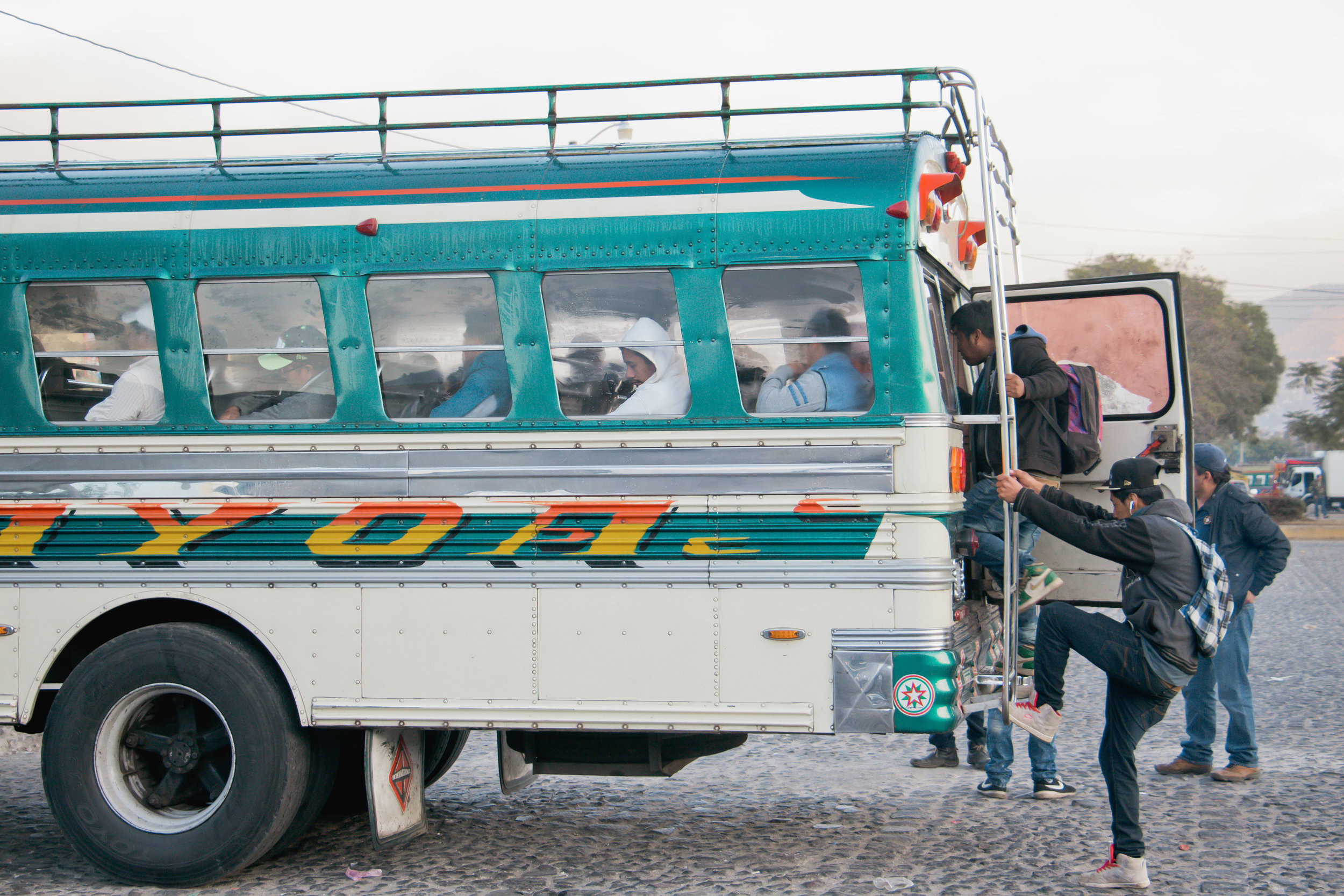 A YOUNG MAN CLIMBS ONTO A CHICKEN BUS EARLY IN THE MORNING IN THE ANTIGUA BUS TERMINAL ON JAN. 10. CHICKEN BUSES ARE A VERY COMMON FORM OF PUBLIC TRANSPORTATION IN GUATEMALA FOR ANY AGE.