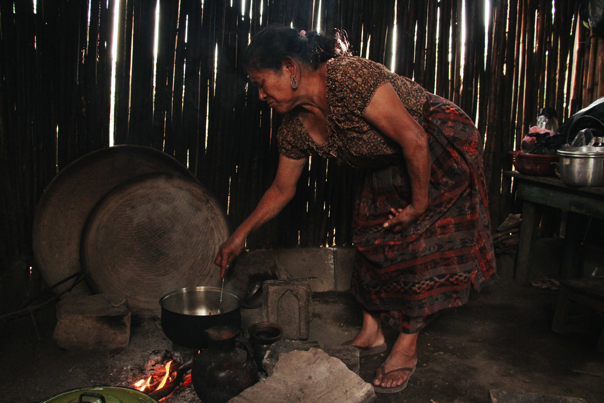 MARIA TRINIDAD SANTOS STIRS HER FOOD OVER THE FIRE IN HER HOME. SANTOS SOLD FOOD IN THE VILLAGE UNTIL 10 P.M.