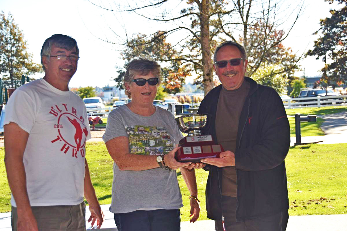 Last year's recipient, Rose Hare presents David Ulis with the Ultra Cup. Left is Club president, Dave McDonald. (Photo: Owen Wong)