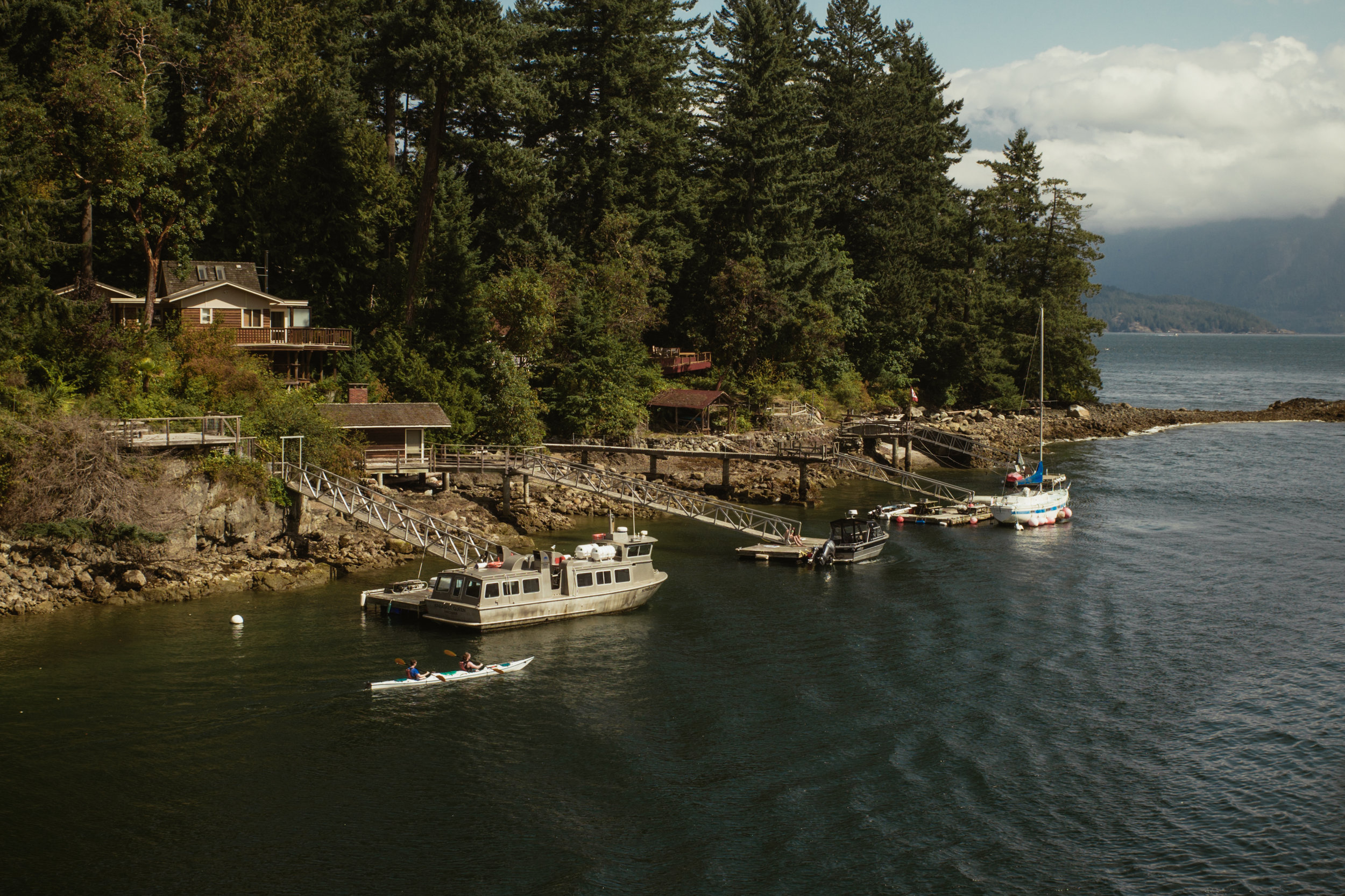 A quick arrival onto Bowen Island's shores, lined with quintessentially quaint island houses, surrounded by glorious trees, docks and boats, just steps away.