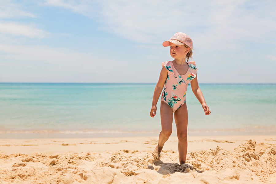 child on the beach wearing a swimsuit and hat