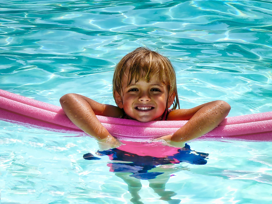 Happy girl hanging on a pool noodle smiling