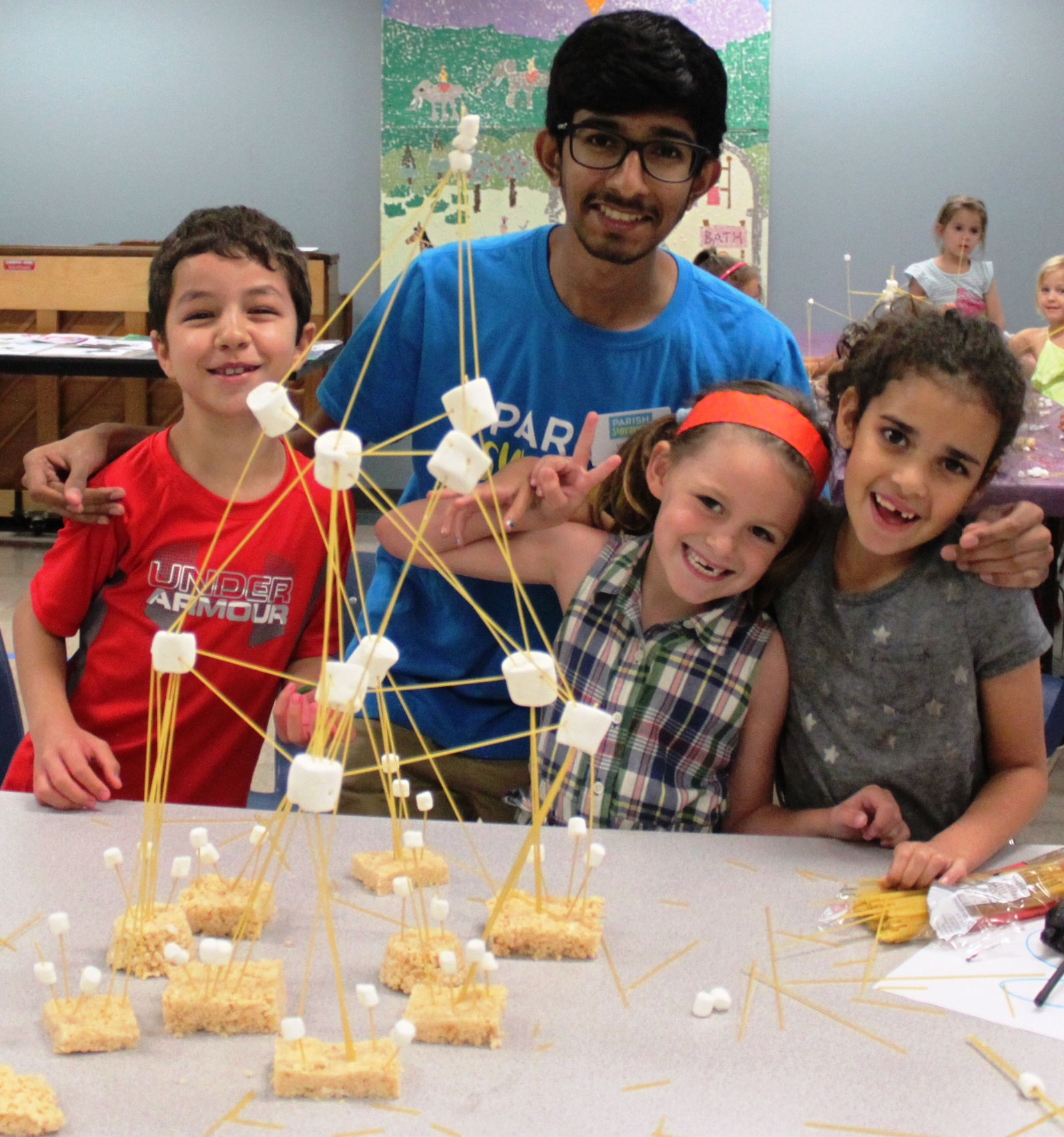 Parish Summer day camp counselor works with a group of kids on a STEM-based challenge during day camp in Dallas, Texas.