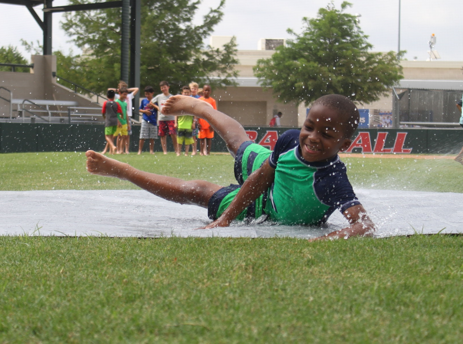 Boy has fun doing the slip and slide during the Baseball Camp at Parish Summer in Dallas, Texas.