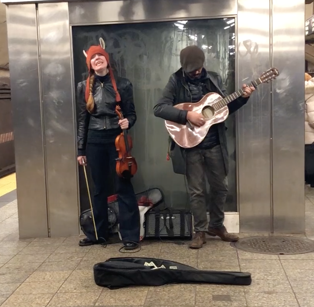 Violinist and guitarist duo playing at Times Square subway platform