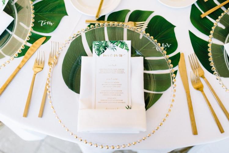 lisa stoner weddings- florida wedding designer- custom wedding menu cards- monstera leaves- gold flatware for a florida wedding- glass charger plate with gold rim.jpg