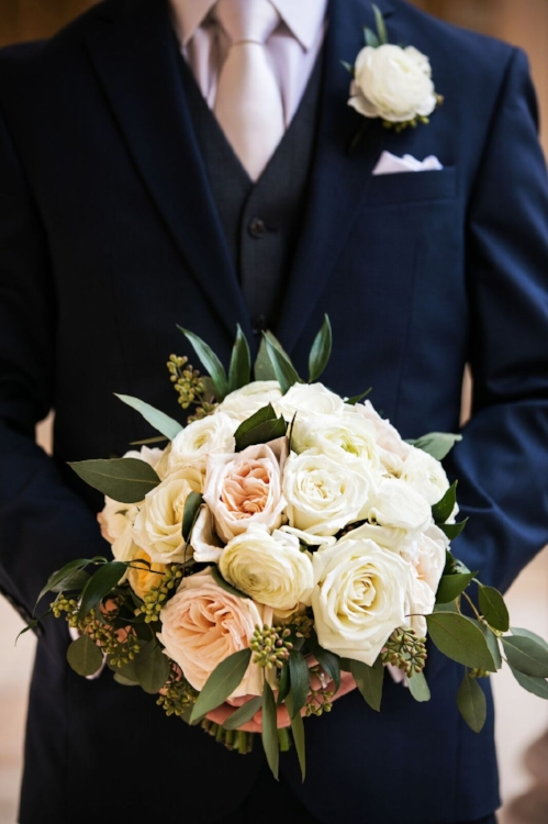lisa stoner event planning - best wedding planner in orlando - groom in a blue suit- groom holding brides bouquet- white and blush bridal bouquet.jpg