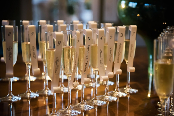 lisa stoner events- champagne toast- champagne - wedding place card - place card scroll on a champagne glass- seating for a wedding - place card.jpg